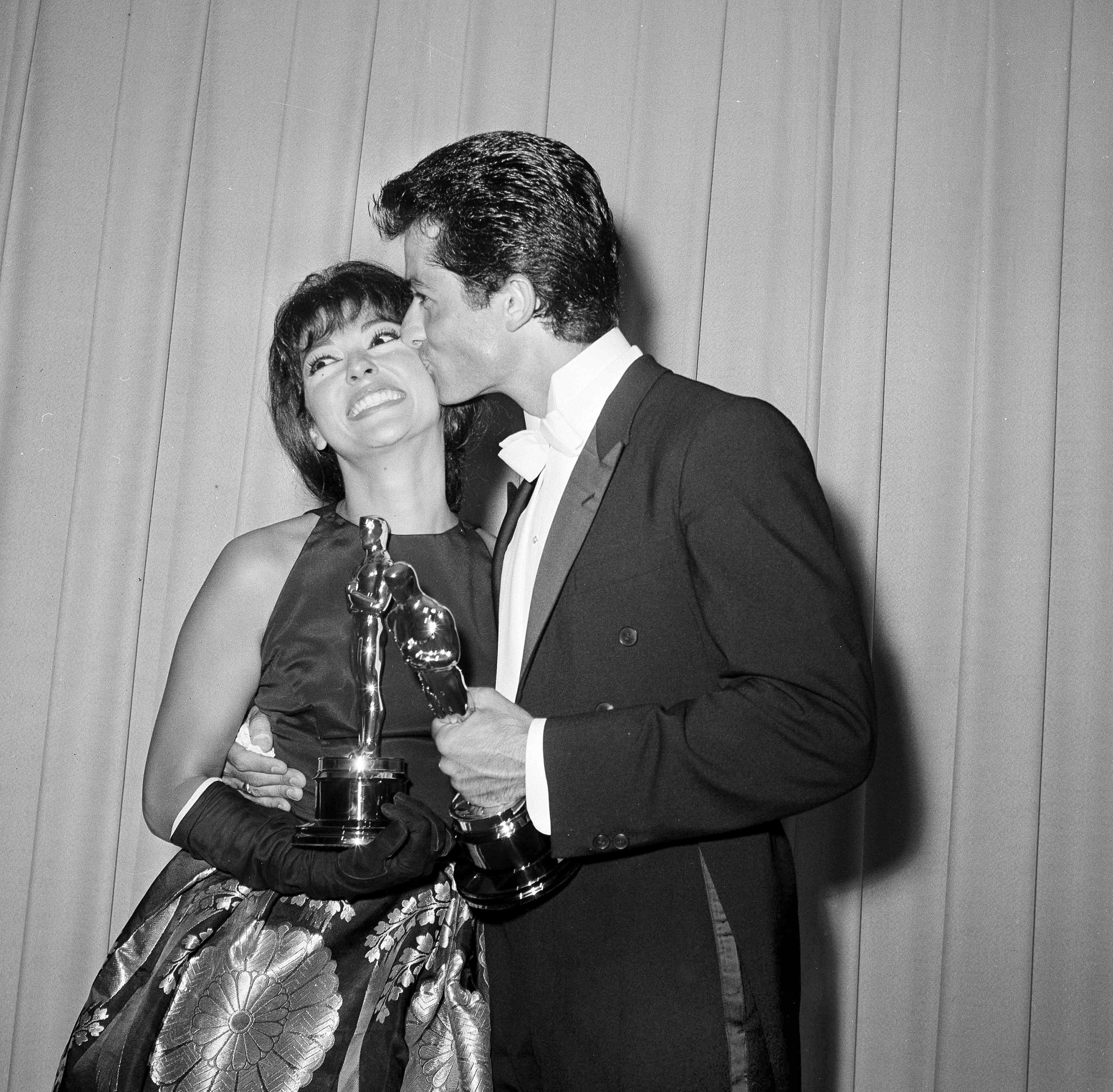 Rita Moreno gets a kiss from dancer and actor George Chakiris after they each won Academy Awards, 1962.
