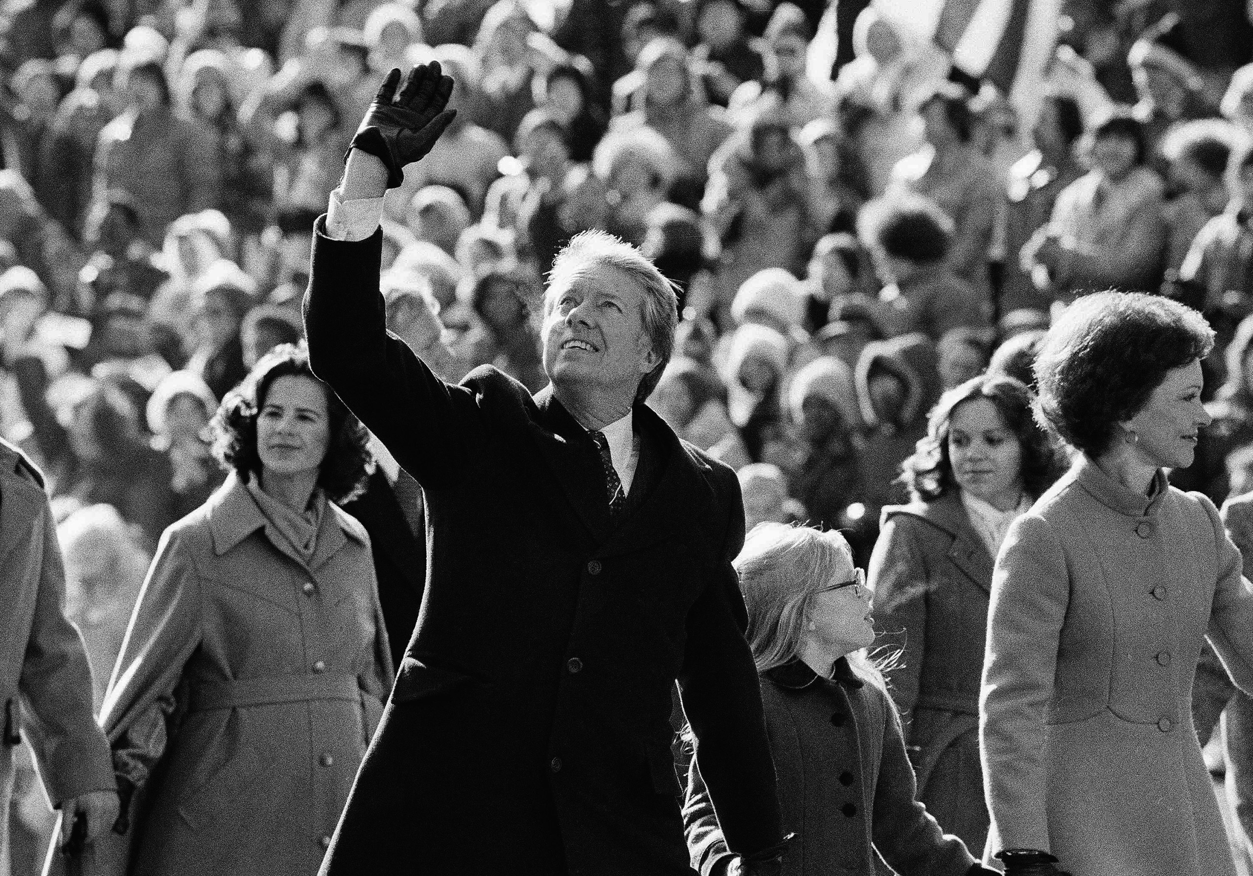 President Jimmy Carter waves to the crowd while walking with his wife Rosalynn along Pennsylvania Avenue and their daughter Amy. The Carters elected to walk the parade route from the Capitol to the White House following his inauguration in Washington, on Thursday, Jan. 20, 1977.