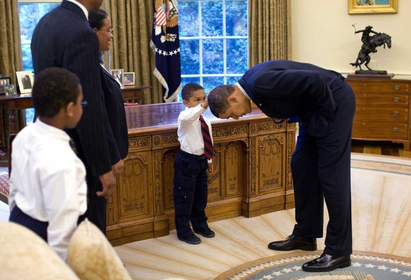 """May 8, 2009""""A temporary White House staffer, Carlton Philadelphia, brought his family to the Oval Office for a farewell photo with President Obama. Carlton's son softly told the President he had just gotten a haircut like President Obama, and asked if he could feel the President's head to see if it felt the same as his.""""(Official White House photo by Pete Souza)This official White House photograph is being made available only for publication by news organizations and/or for personal use printing by the subject(s) of the photograph. The photograph may not be manipulated in any way and may not be used in commercial or political materials, advertisements, emails, products, promotions that in any way suggests approval or endorsement of the President, the First Family, or the White House."""