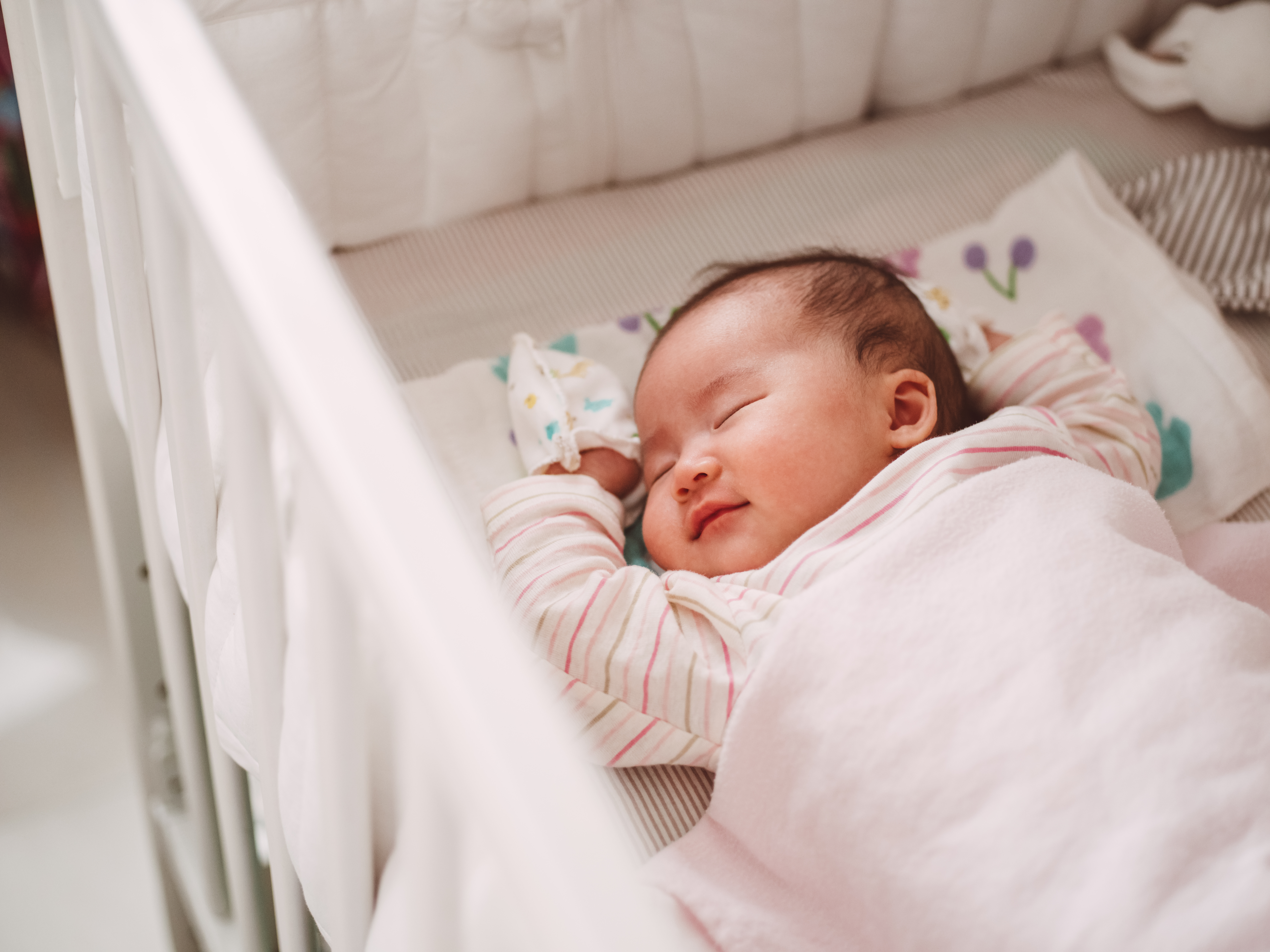 Adorable new born baby smiling sweetly while sleeping soundly in the crib