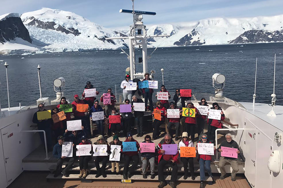 Protestors holding up signs reading  Penguins March for Peace  from Paradise Bay, Antarctica, on Jan. 21, 2016.