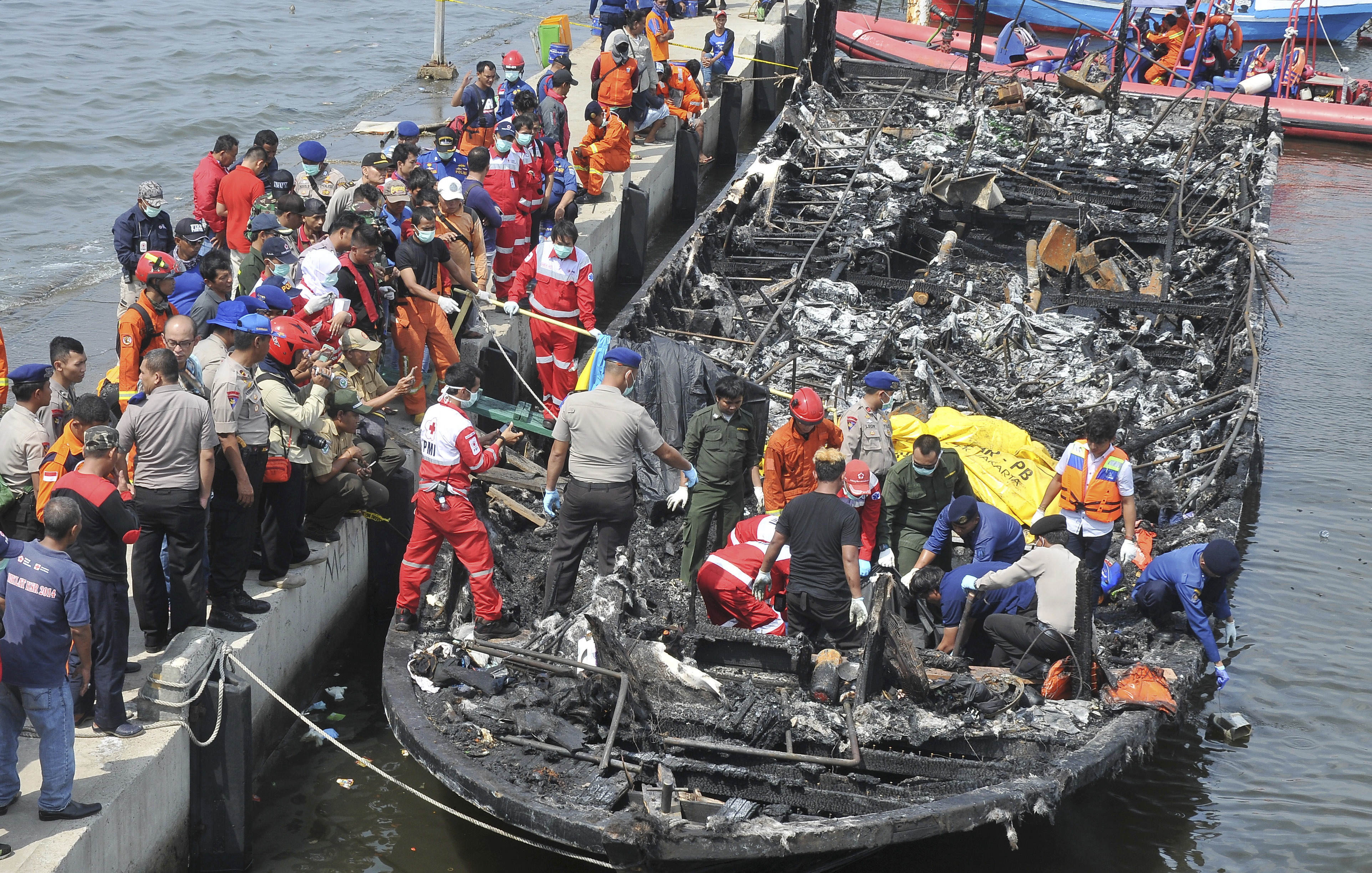Rescuers search for victims from the wreckage of a ferry that caught fire off the coast of Jakarta on Jan. 1, 2017.