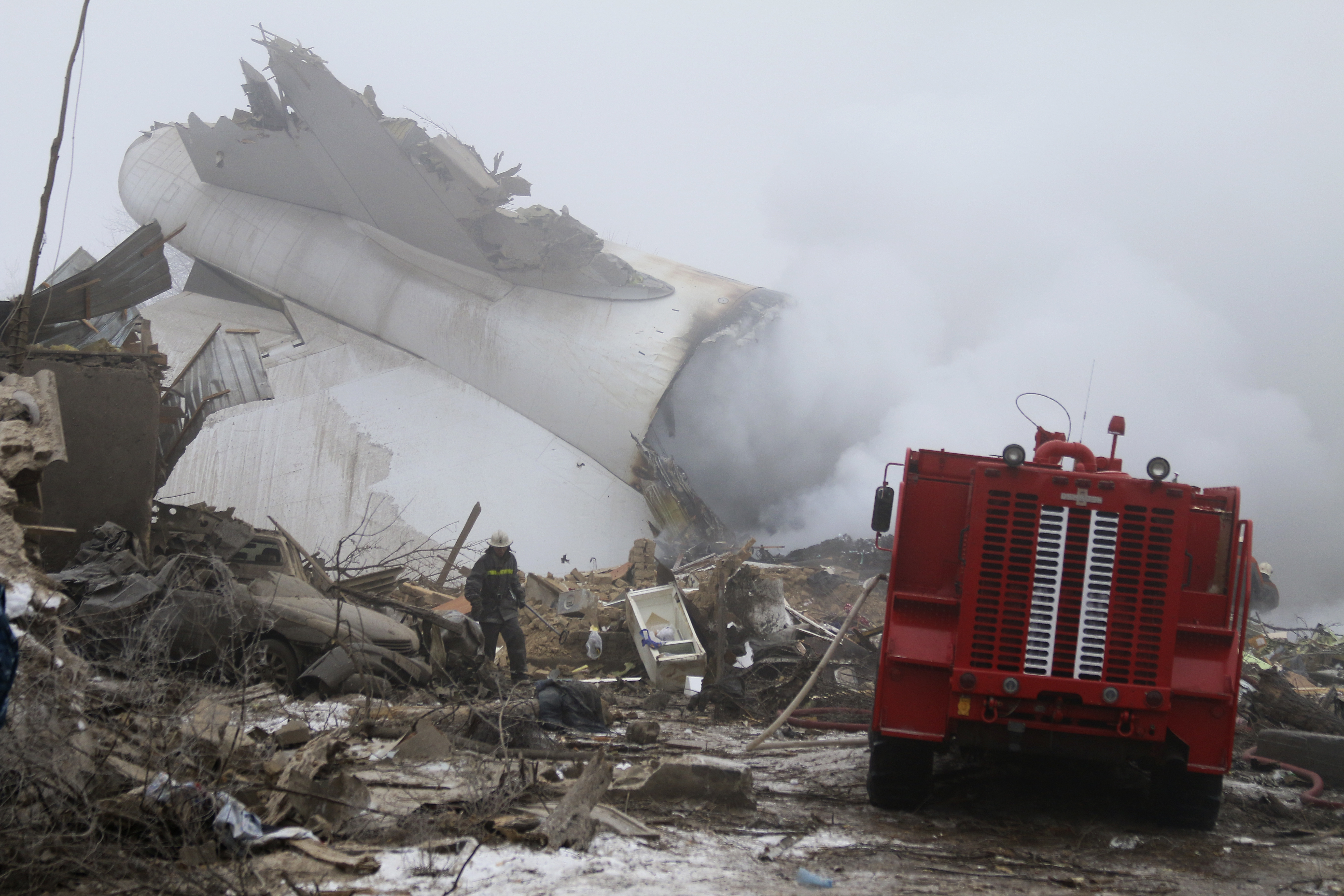A Kyrgyz firefighter inspects a plane crash site outside Bishkek, Kyrgyzstan, Jan. 16, 2017.