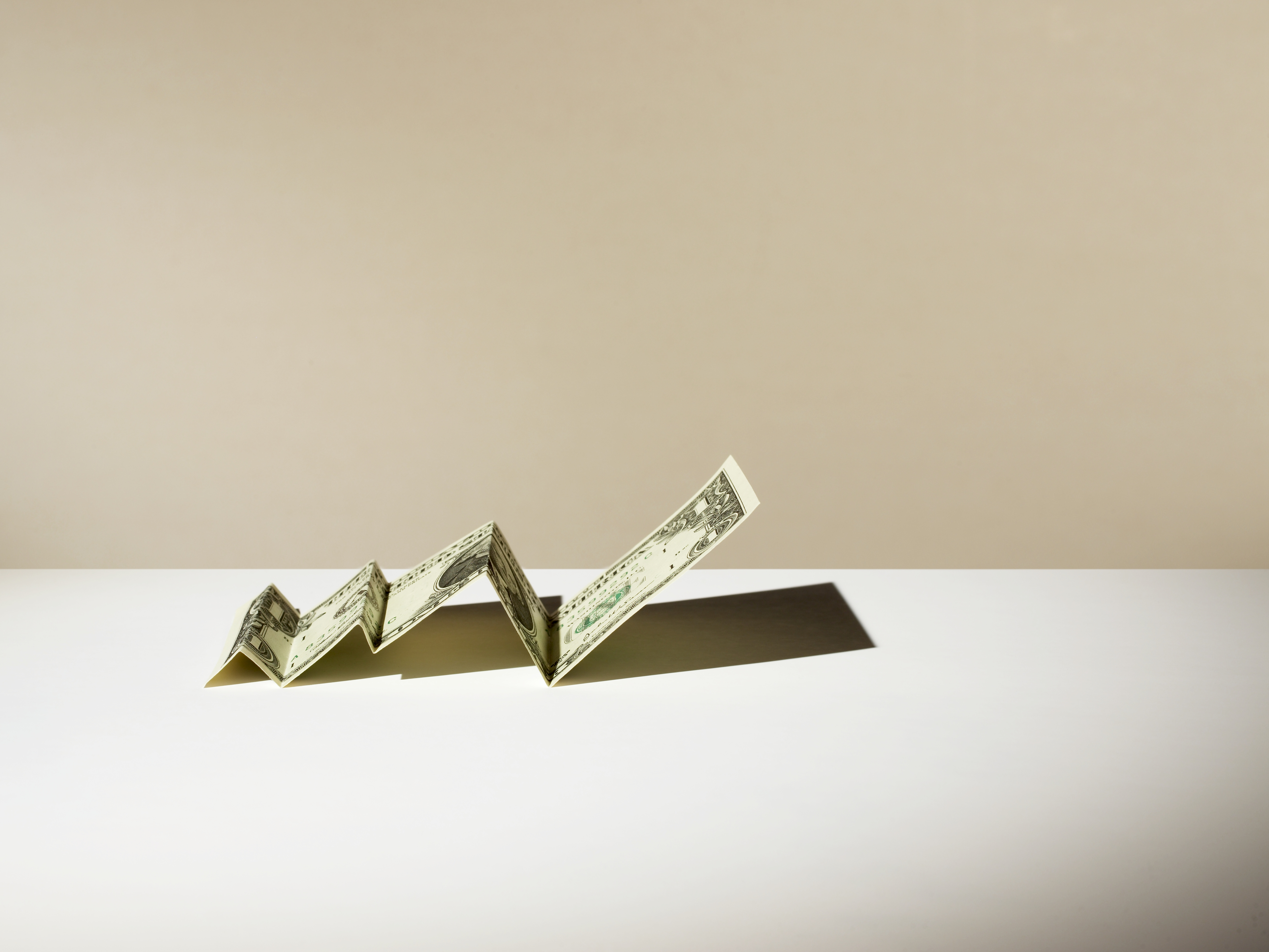 Us Dollar note folded to a line graph