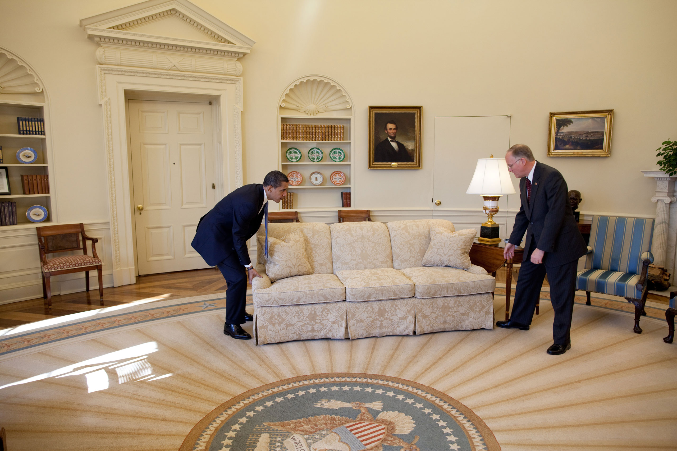 """""""White House valets had moved the sofas in the Oval Office to accommodate the large number of press photographers that were covering the President's meeting with Vermont Gov. Jim Douglas. When the photo-op ended, the President said to Gov. Douglas, 'let's move the sofas back in place.' Gov. Douglas didn't quite know what to do as the President did the heavy lifting. The valets now good-naturedly cringe when they look at this picture because it was their responsibility to move the sofas back in place,"""" Feb. 2, 2009."""