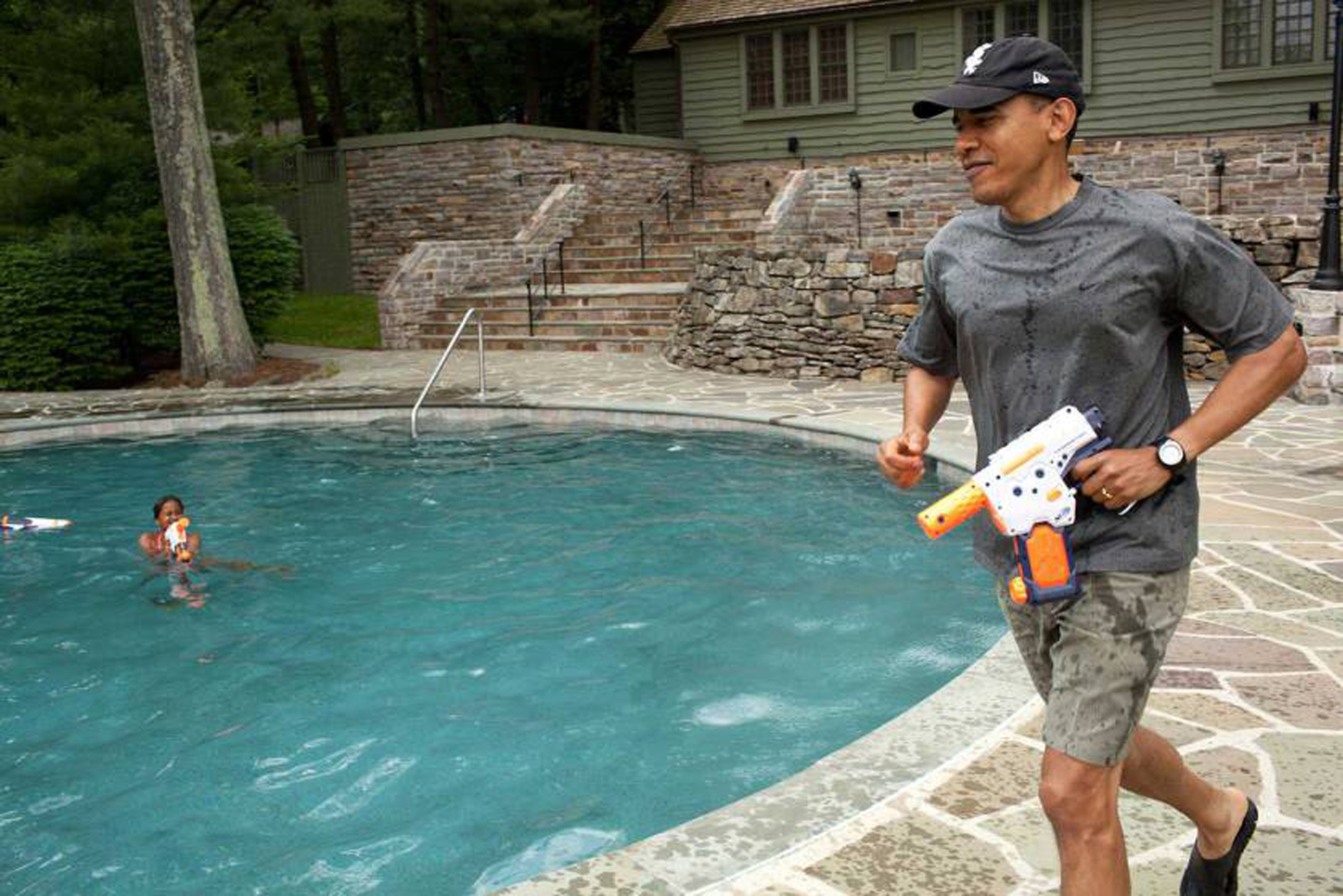 President Obama joins in a water gun fight with daughter Sasha during her 10th birthday celebration at Camp David, Md., June 11, 2011.