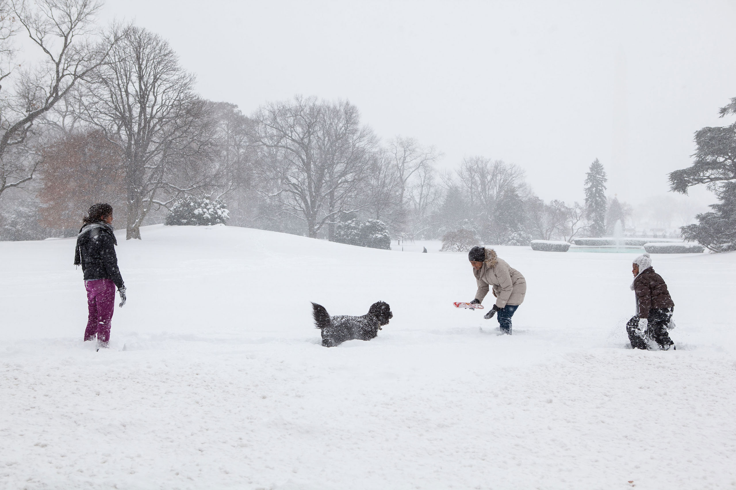 First Lady Michelle Obama and daughters Sasha and Malia, along with family dog, Bo, play in the snow on the South Lawn of the White House on Saturday, Dec. 19, 2009.