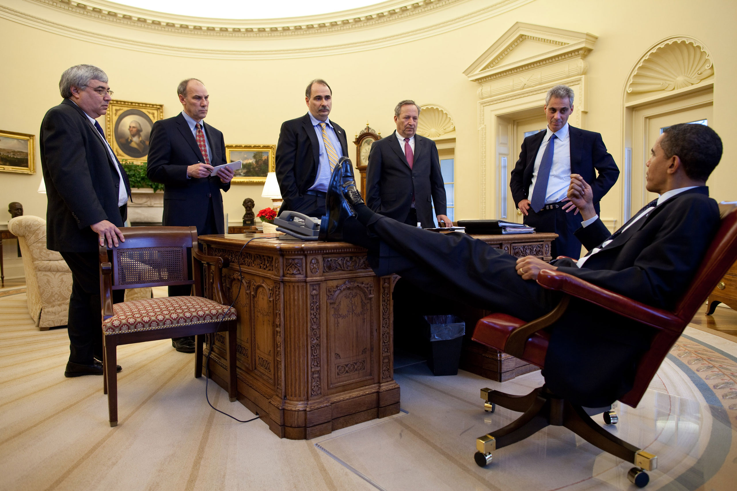 """""""The President talks with aides during an impromptu meeting around the Resolute desk,"""" Feb. 4, 2009."""