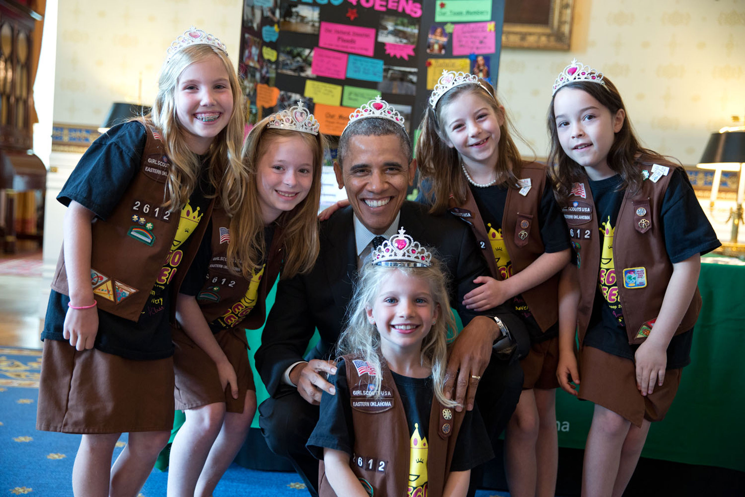This photograph was from the annual White House Science Fair. It shows the President posing with Girl Scout Troop 2612 from Tulsa, Oklahoma. I think the 8-year-old girls — Avery Dodson, Natalie Hurley, Miriam Schaffer, Claibyre Winton and Lucy Claire Sharp — are called 'Brownies.' They had just shown the President their exhibit: a Lego flood-proof bridge project. The fair celebrated the student winners of a broad range of science, technology, engineering, and math (STEM) competitions from across the country,  May 24, 2014.