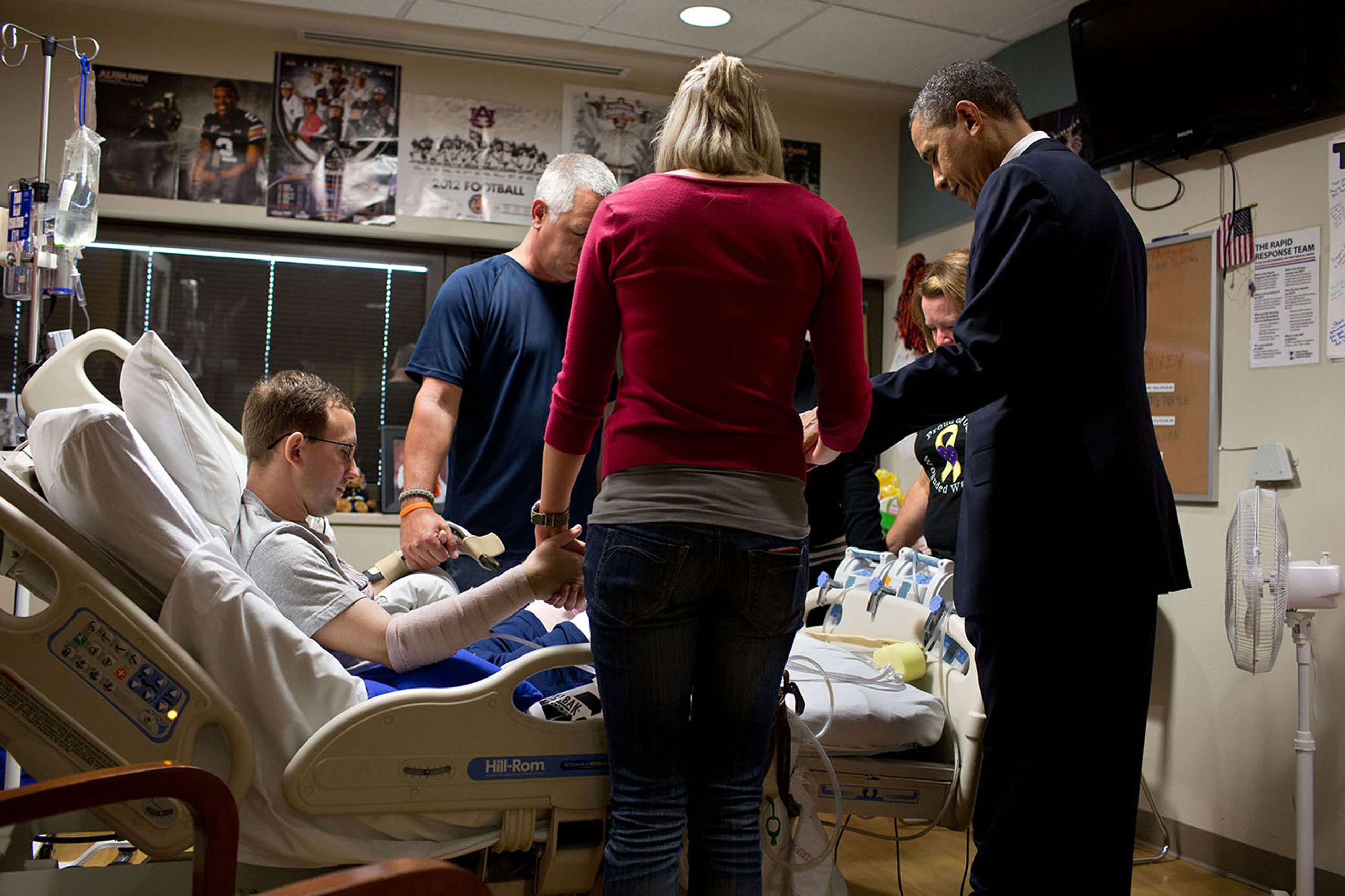 The President prays with a wounded service member and his family during a visit to Walter Reed National Military Medical Center in Bethesda, Md. The President likes to make a few trips a year to Walter Reed to visit wounded warriors and their families,  June 28, 2012.