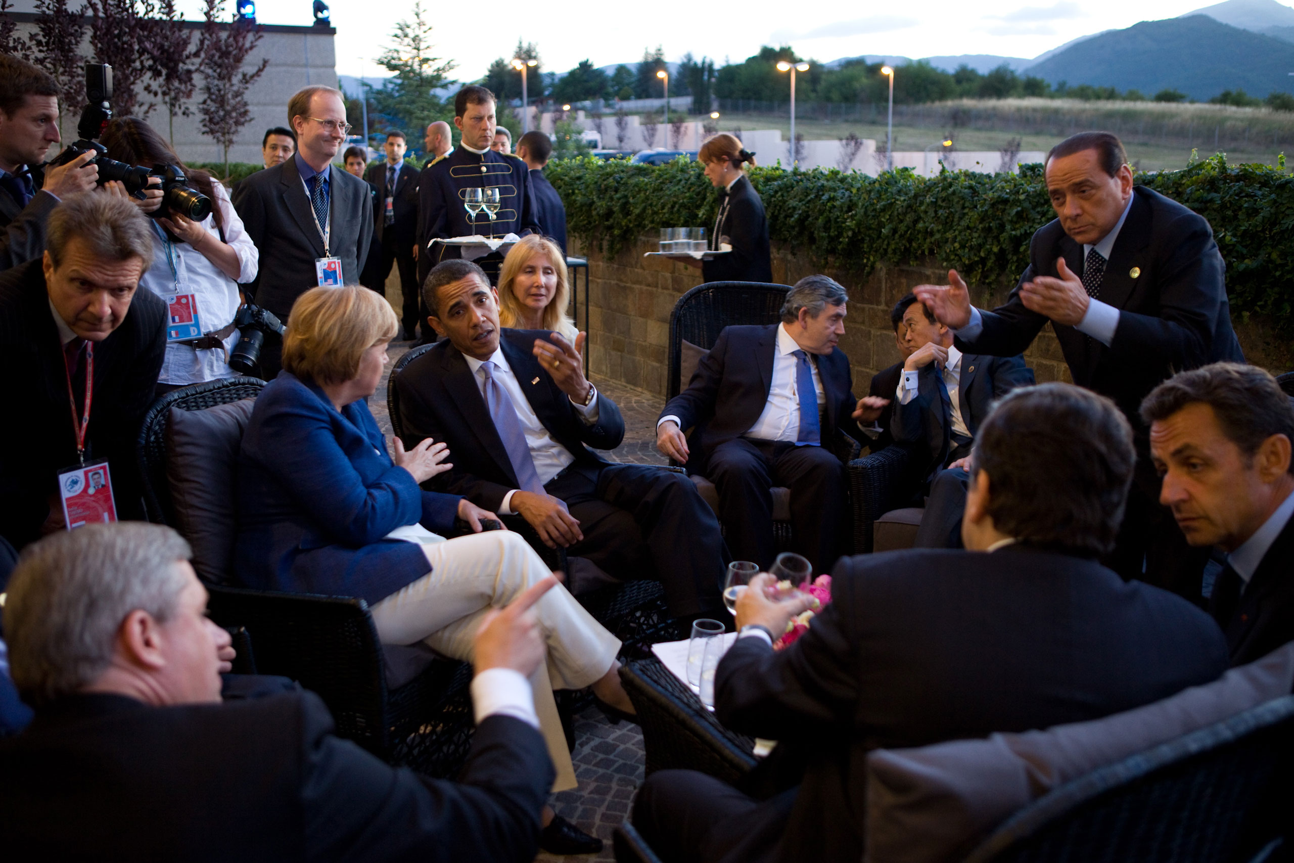 """""""This was a great scene just before dinner at the G-8 Summit in L'Aquila, Italy. As the leaders arrived, they spontaneously moved to a small patio outside. Several different conversations were taking place. Finally as dusk settled in, Italian Prime Minister Silvio Berlusconi, at far right, motioned for everyone to move inside for the dinner,""""July 8, 2009."""