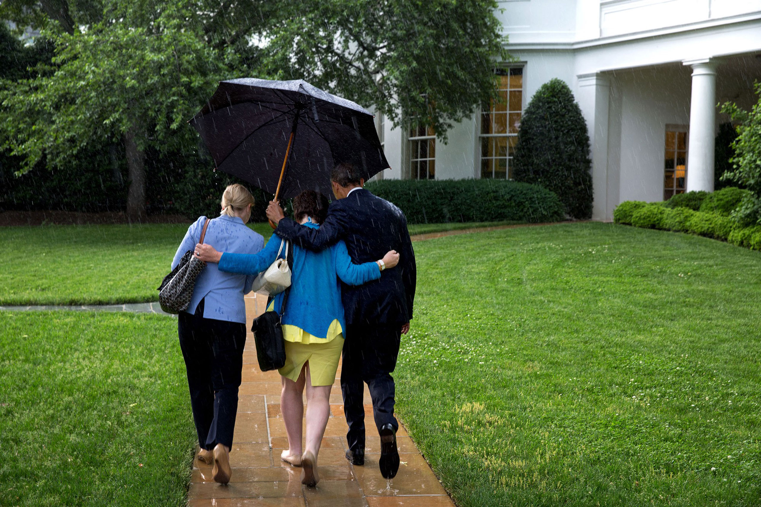 After returning on Marine One, the President walks from the helicopter to the Oval Office holding an umbrella for aides Valerie Jarrett and Anita Decker Breckenridge,  May 18, 2015.