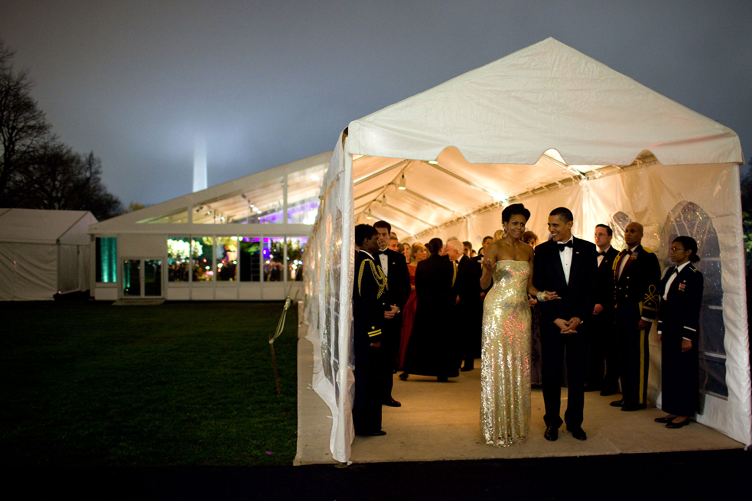 """""""The President and First Lady wait for Indian Prime Minister Singh's motorcade to depart the White House at the conclusion of the first official state dinner for the Obama administration, Nov. 24, 2009. The dinner was held in a tent on the South Lawn. The mist and fog made for an interesting scene, even obscuring the top of the Washington Monument in the background."""""""