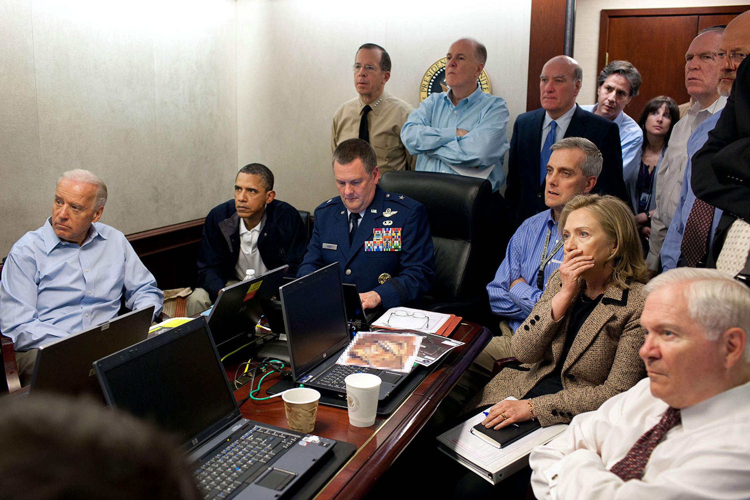 Much has been made of this photograph that shows the President and Vice President and the national security team monitoring in real time the mission against Osama bin Laden, May 1, 2011. Some more background on the photograph: The White House Situation Room is actually comprised of several different conference rooms. The majority of the time, the President convenes meetings in the large conference room with assigned seats. But to monitor this mission, the group moved into the much smaller conference room. The President chose to sit next to Brigadier General Marshall B.  Brad  Webb, Assistant Commanding General of Joint Special Operations Command, who was point man for the communications taking place. With so few chairs, others just stood at the back of the room. I was jammed into a corner of the room with no room to move. During the mission itself, I made approximately 100 photographs, almost all from this cramped spot in the corner. Please note: a classified document seen in front of Sec. Clinton has been obscured.