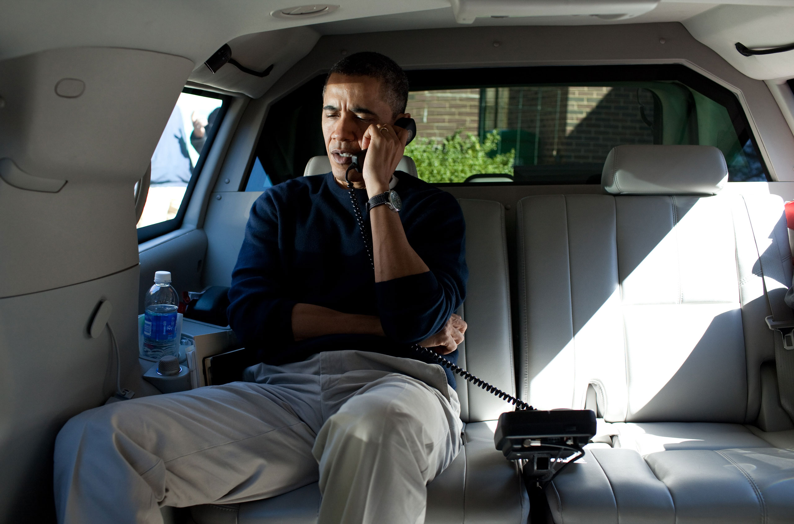 President Barack Obama talks on the phone with Afghanistan President Hamid Karzai from his vehicle outside the Jane E. Lawton Community Center in Chevy Chase, Maryland, Sunday, March 11, 2012.