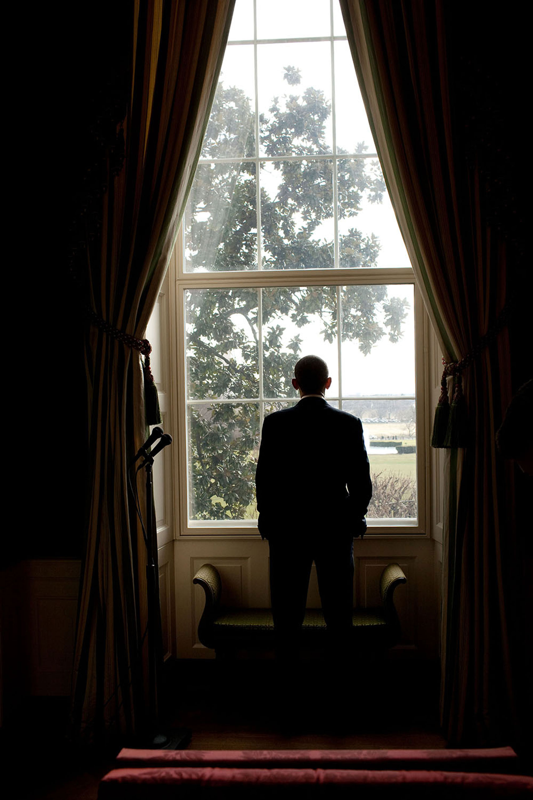 """""""While waiting to be introduced for an event in the East Room of the White House, the President looks out a window in the Green Room towards a view of the Washington Monument and Jefferson Memorial,"""" Jan. 6, 2010."""