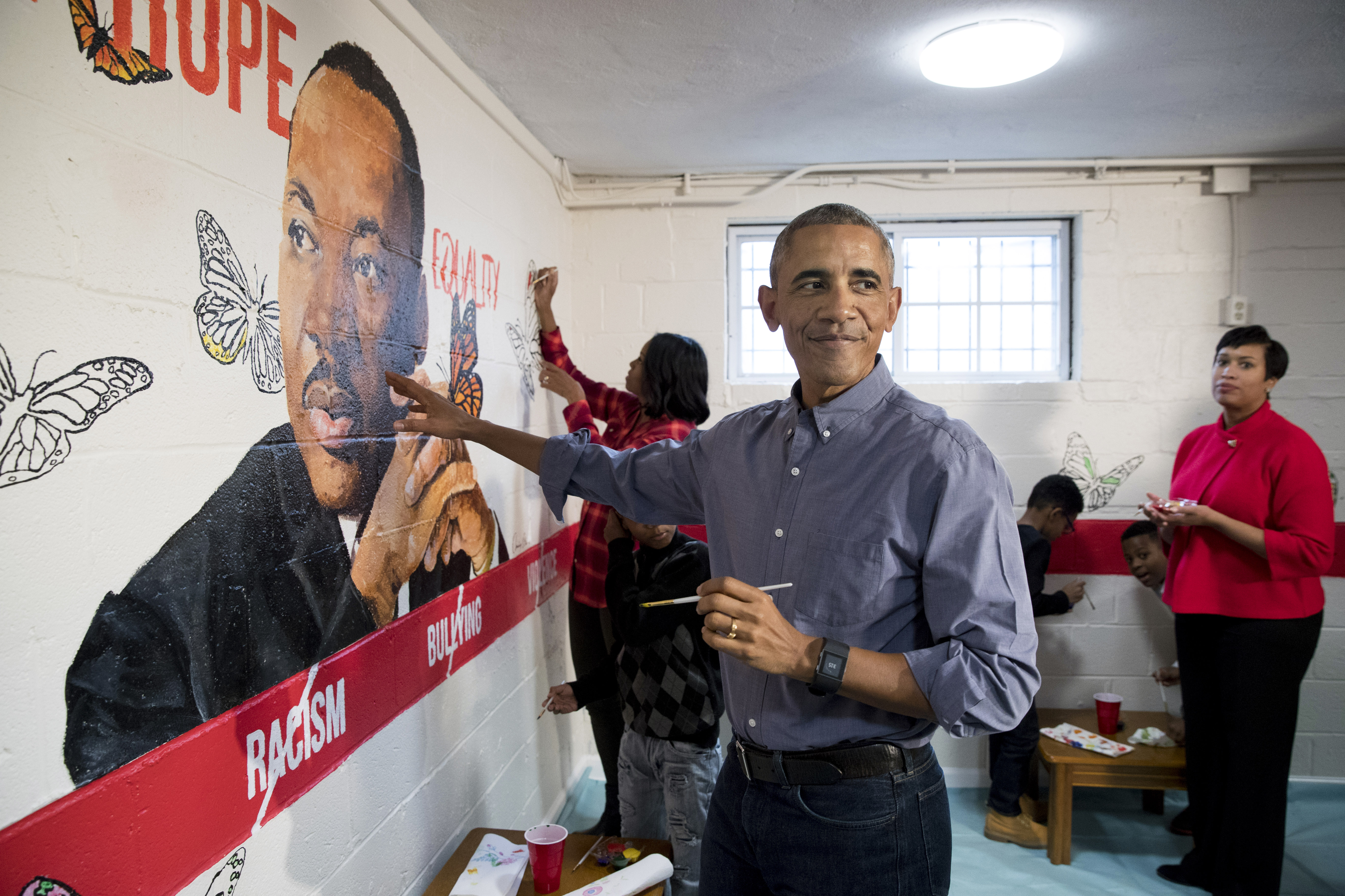 WASHINGTON, DC - JANUARY 16: (AFP OUT) U.S. President Barack Obama (Front) and First Lady Michelle Obama (Back) help paint a mural depicting Martin Luther King Jr., as Mayor of Washington DC Muriel Bowser (R) looks on, at the Jobs Have Priority Naylor Road Family ShelterJanuary 16, 2017 in Washington, DC. President Obama and the First Lady attended a service event at the Jobs Have Priority Naylor Road Family Shelter for Martin Luther King Jr. Day. (Photo by MICHAEL REYNOLDS-Pool/Getty Images)