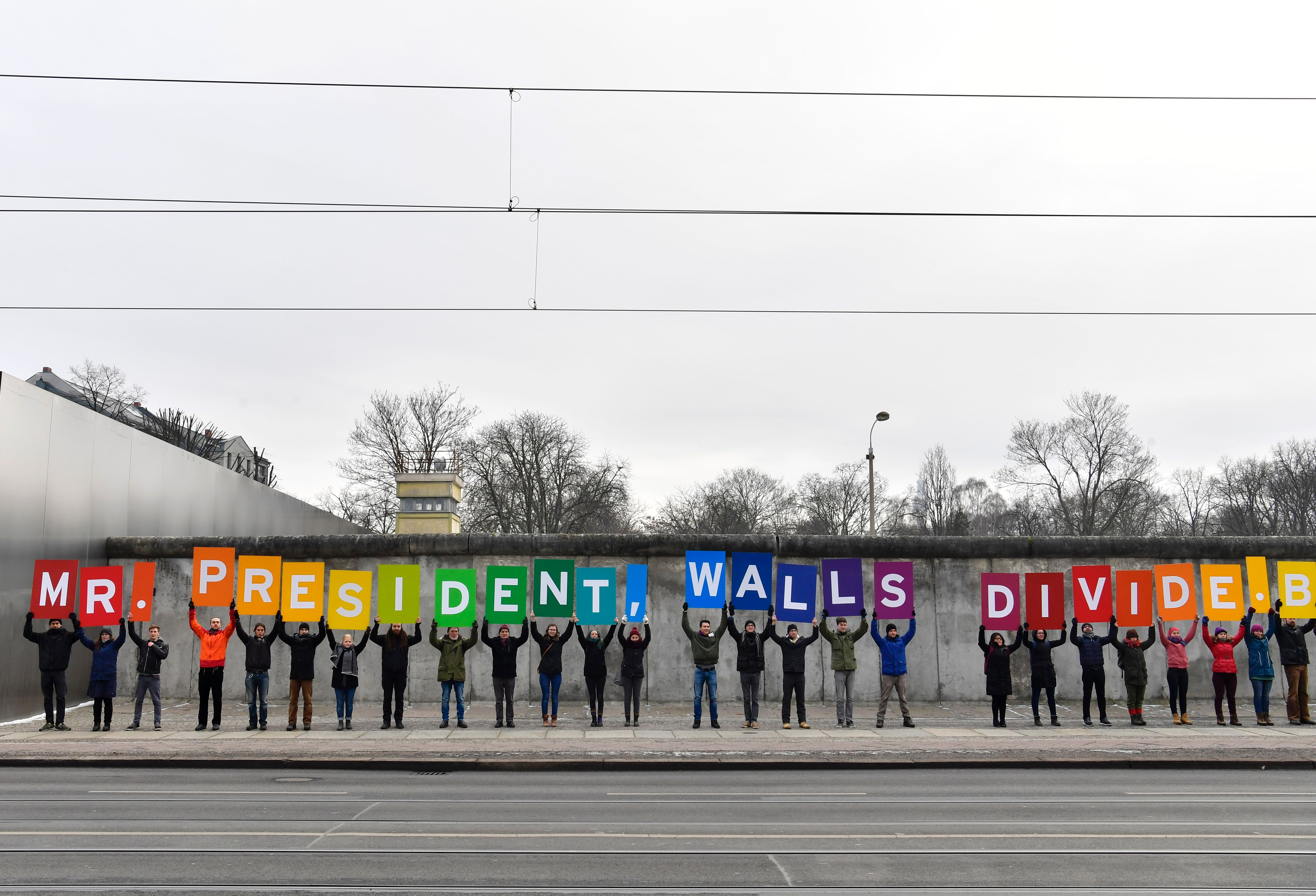 Activists from Greenpeace display a message reading  Mr. President, walls divide. Build Bridges!  along the Berlin wall in Berlin on Jan. 20, 2017 to coincide with the inauguration of U.S. President Donald Trump.