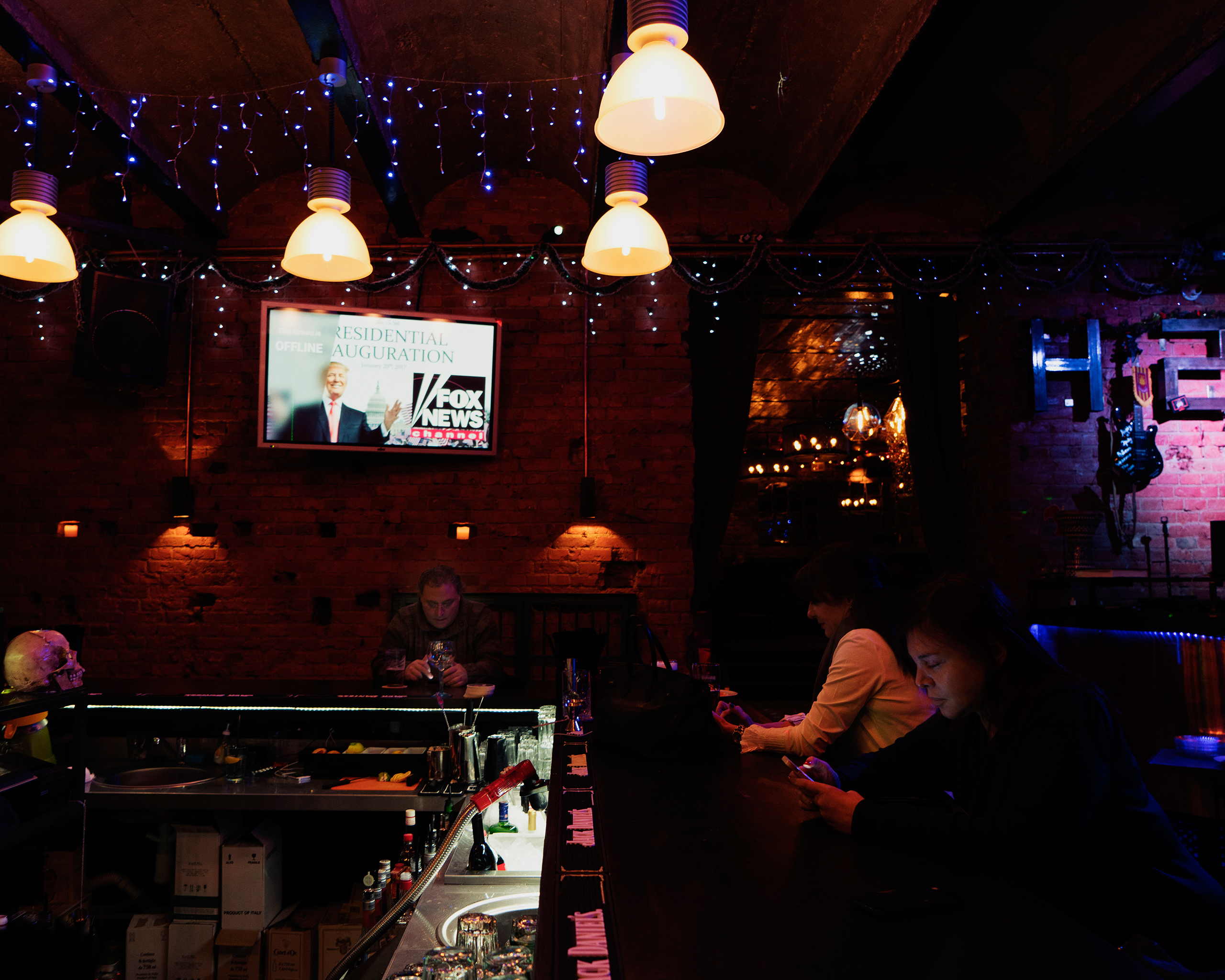 A small gaggle of American expatriates await the televised inaugural ceremonies for Donald Trump at H2 Bar in central Moscow on Jan. 20, 2017.