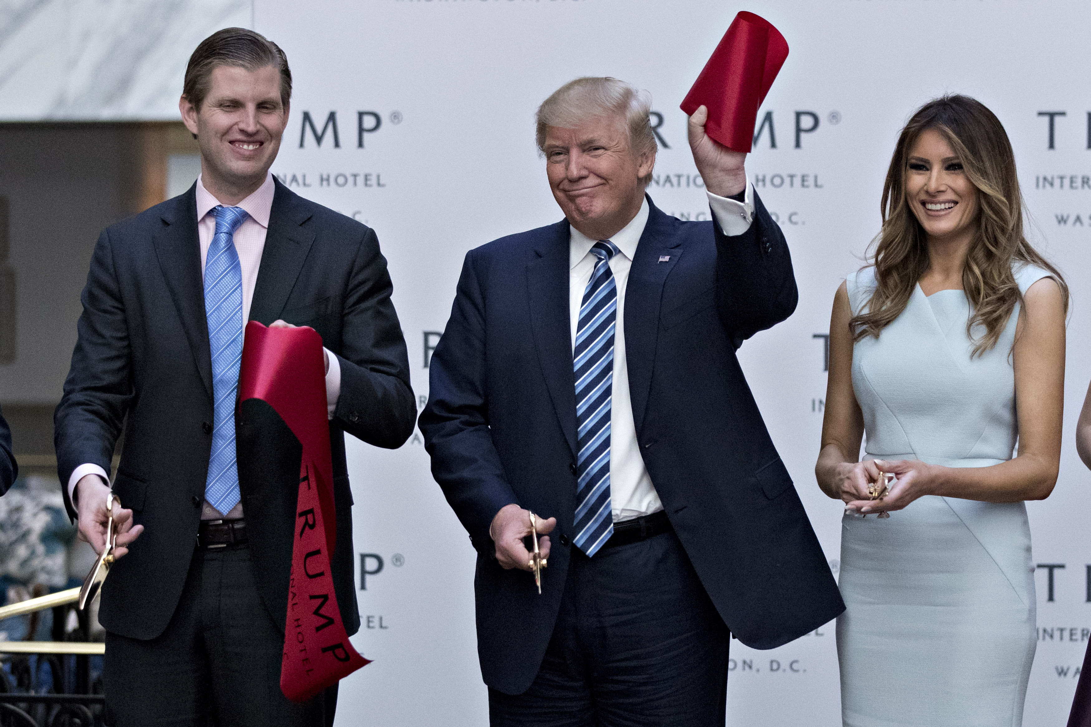 Donald Trump holds a piece of ribbon next to his wife Melania Trump, right, and his son Eric Trump during the grand opening ceremony of the Trump International Hotel in Washington, D.C., U.S., on Wednesday, Oct. 26, 2016.