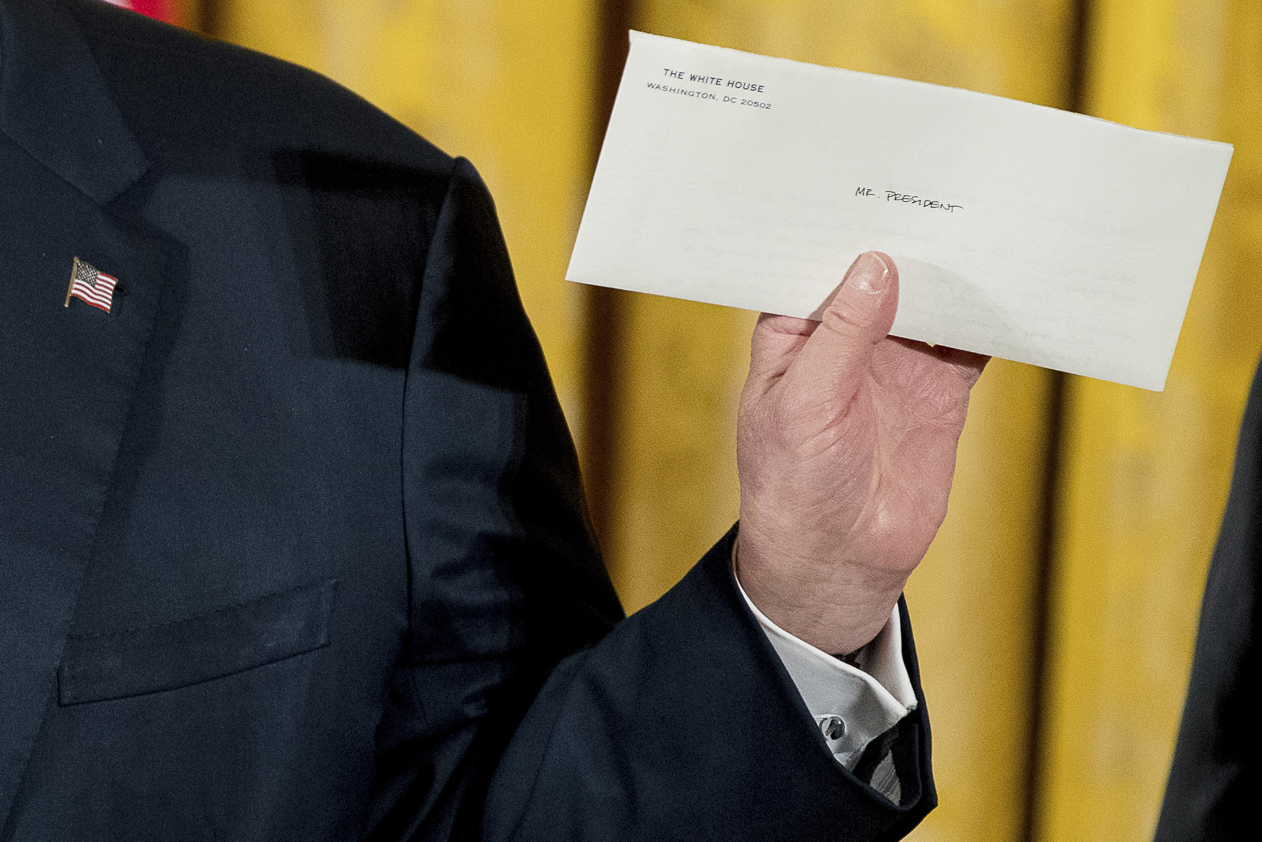 President Donald Trump holds up a letter left for him by former President Barack Obama as he speaks at a White House senior staff swearing in ceremony in the East Room of the White House, on Jan. 22, 2017.