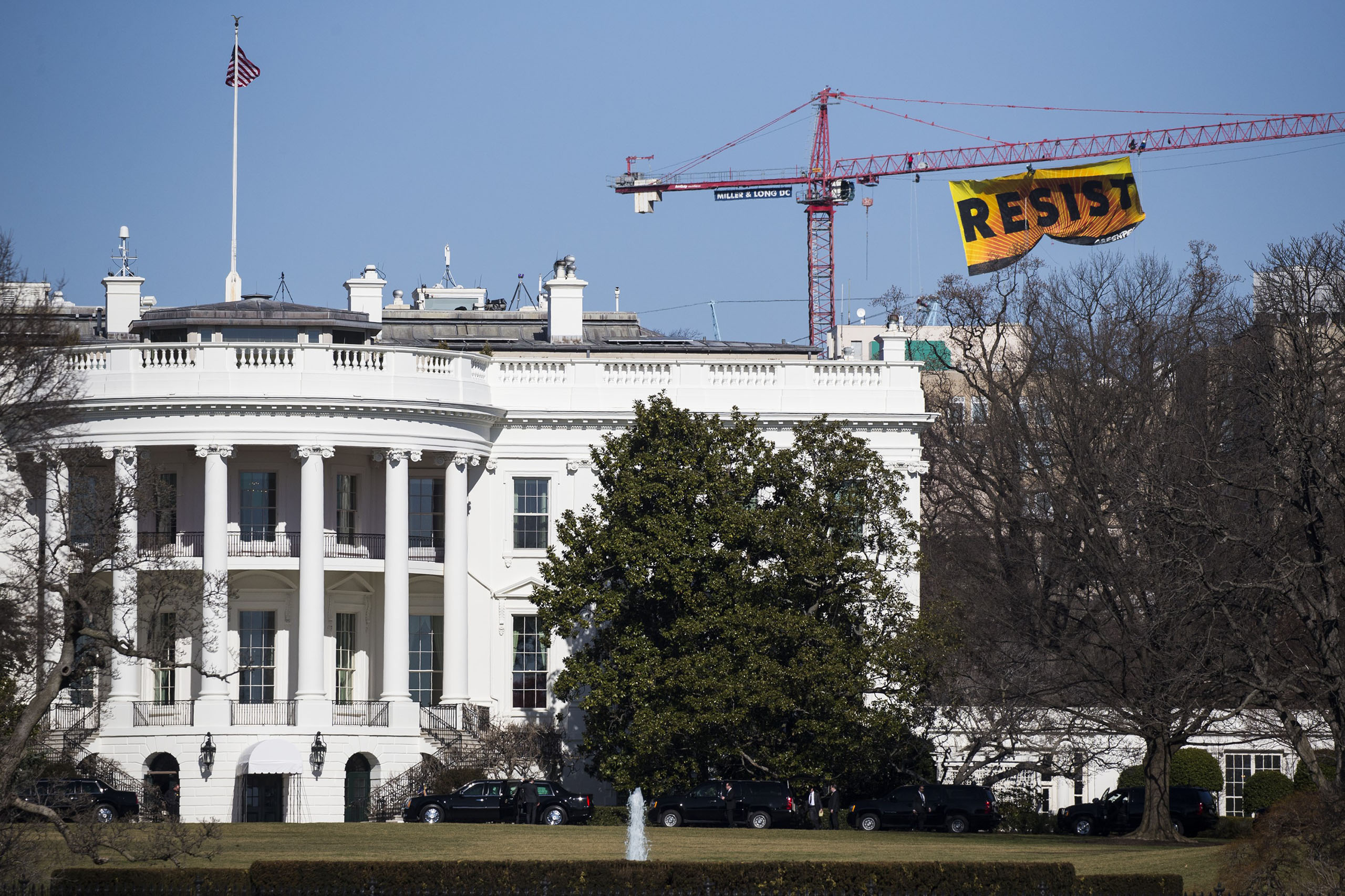 """A sign saying """"resist"""" hung from a construction crane by protestors, with the group Greenpeace, can be seen near the White House, on Jan. 25, 2017."""