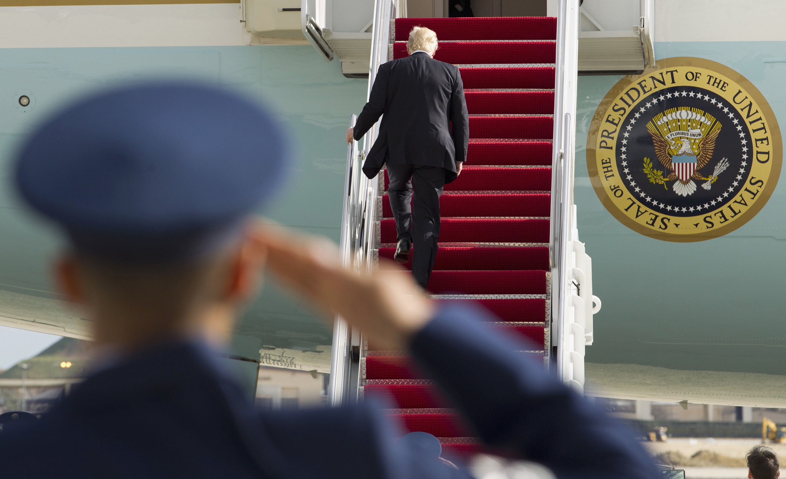 President Donald Trump is saluted as he walks up the stairs of Air Force One before departure from Andrews Air Force Base, Md., on Jan. 26, 2017.