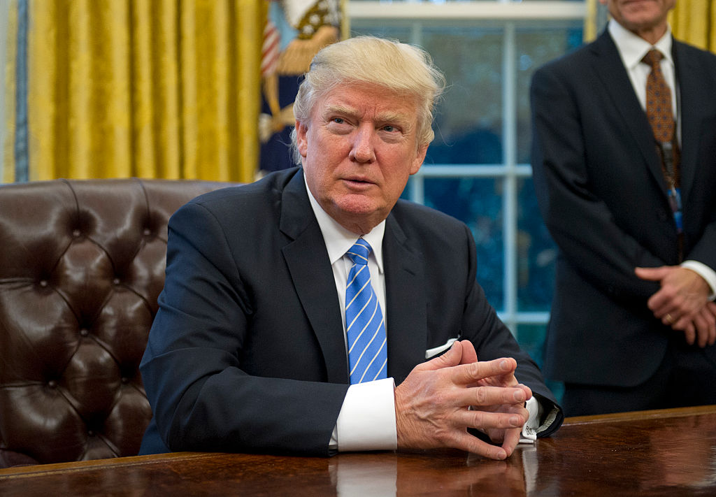 U.S. President Donald Trump prepares to sign three Executive Orders in the Oval Office of the White House in Washington, DC on Monday, January 23, 2017.