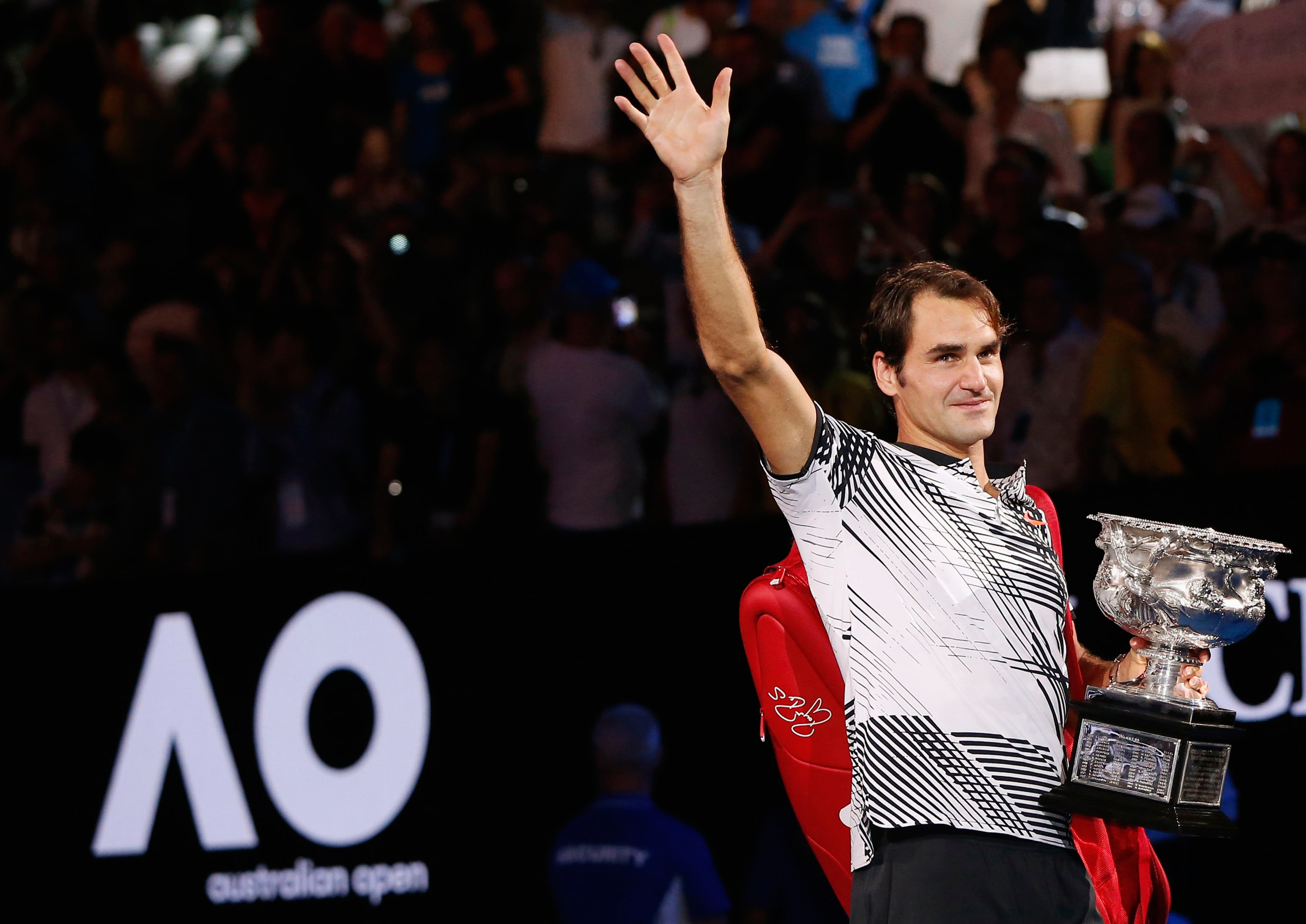 Switzerland's Roger Federer holds the trophy as he celebrates after winning his Men's singles final match against Spain's Rafael Nadal in Melbourne on Jan 29, 2017.