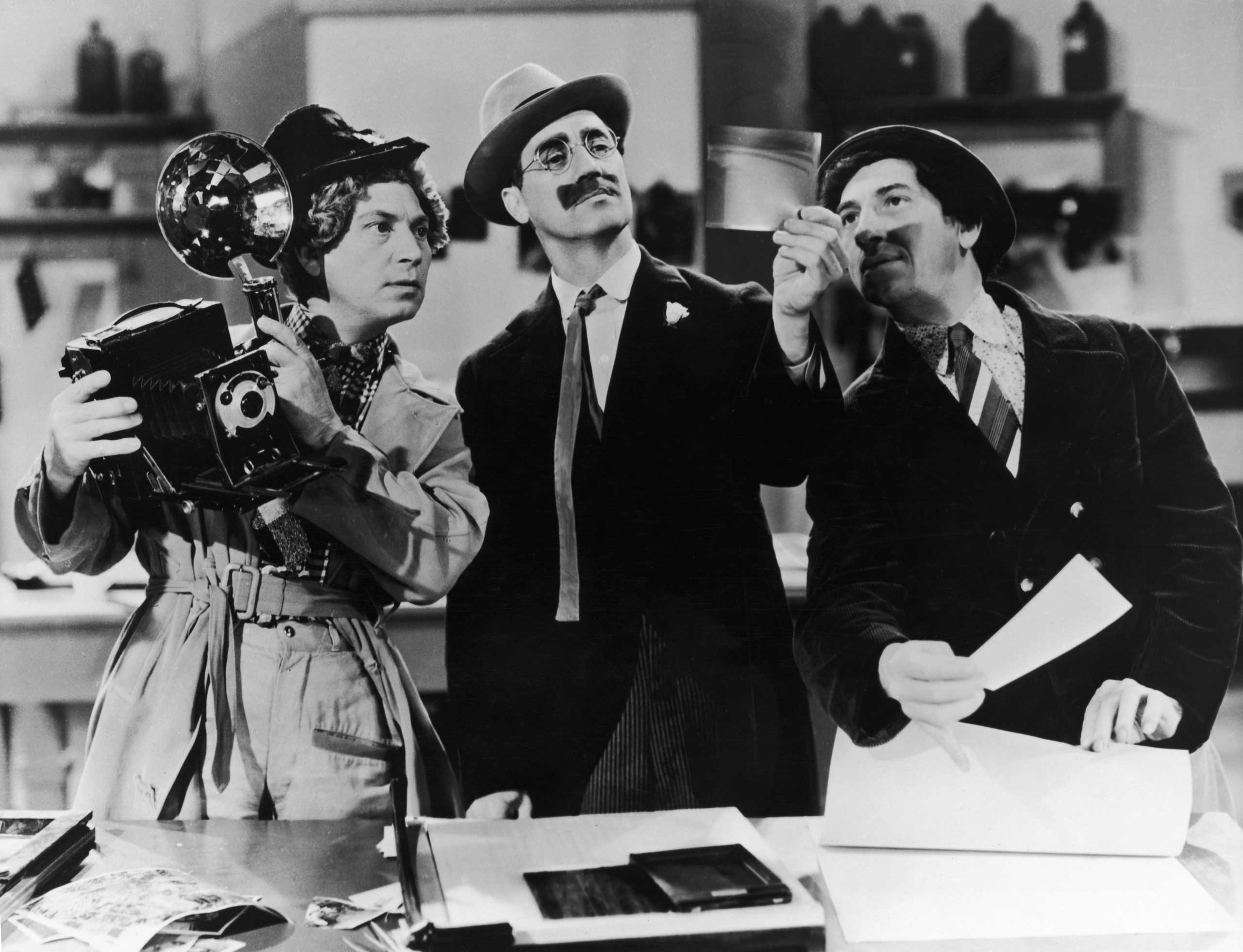 Harpo Marx, Groucho Marx and Chico Marx examining the negatives from a photo-finish in a scene from the comedy 'A Day at the Races', directed by Sam Wood, 1937.