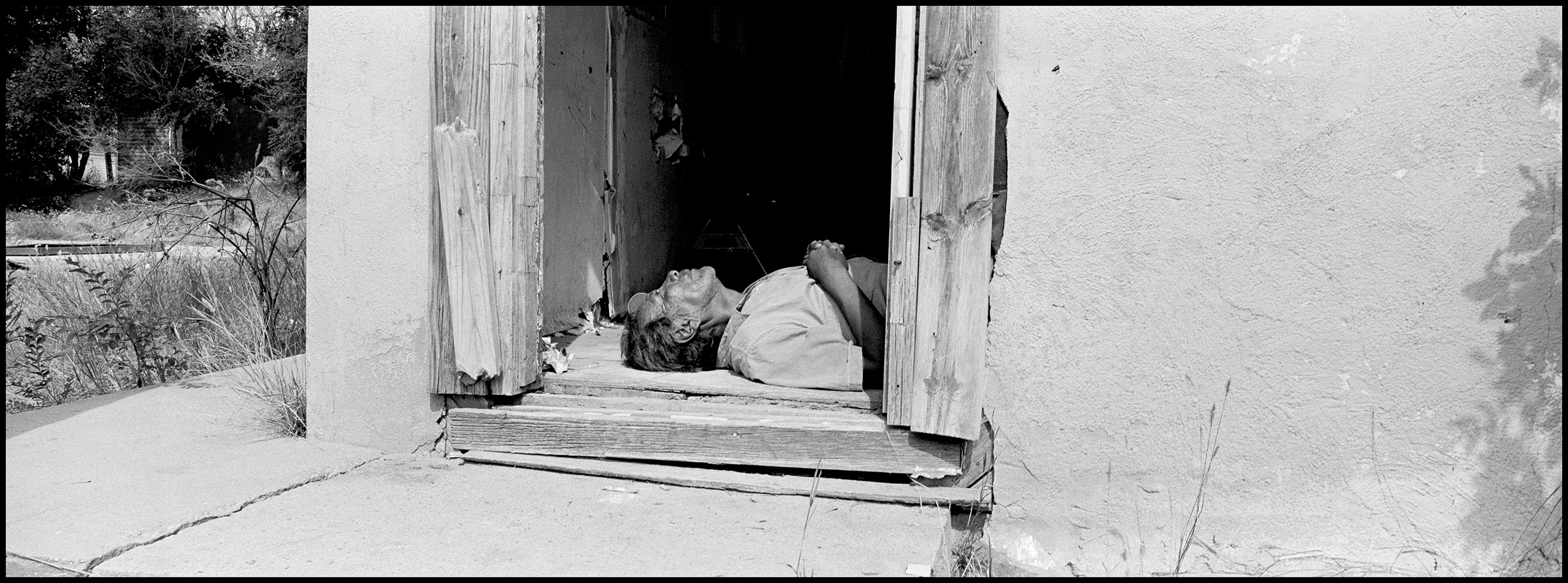Man passed out in doorway of abandoned home used for parties and drinking binges. Pine Ridge, South Dakota, 2015.