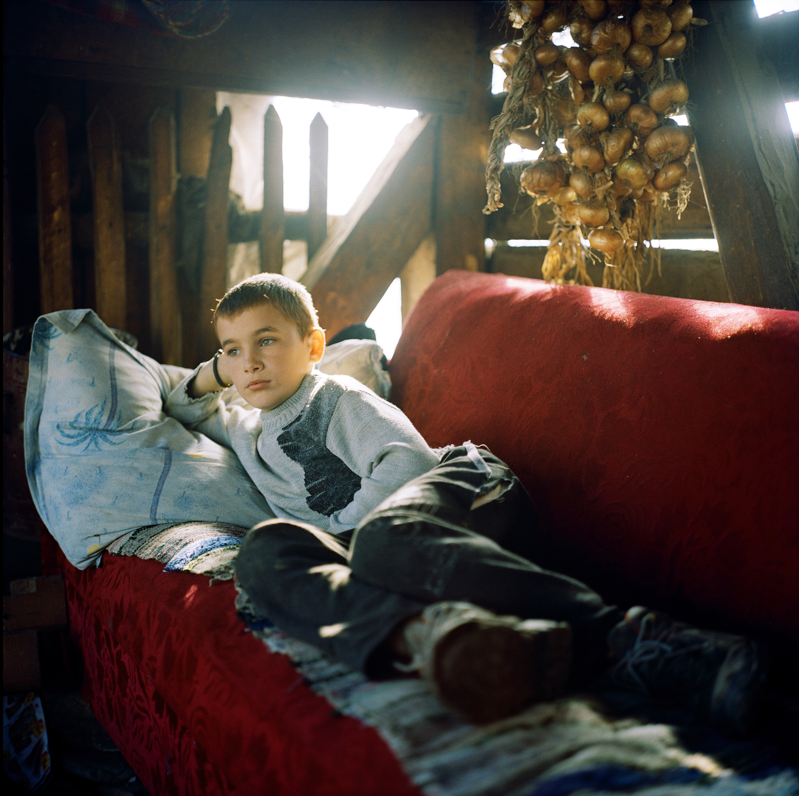 Andrei Rus, 12, relaxes in his father's palinca still in Strâmtura, Maramures, Romania, November, 2012.