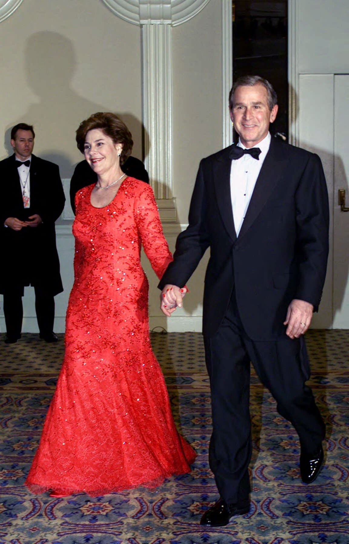 Laura Bush, Michael Faircloth, 2001: For her husband's first inauguration, Bush wore a red, crystal-embroidered Chantilly lace gown designed by a fellow Texan.