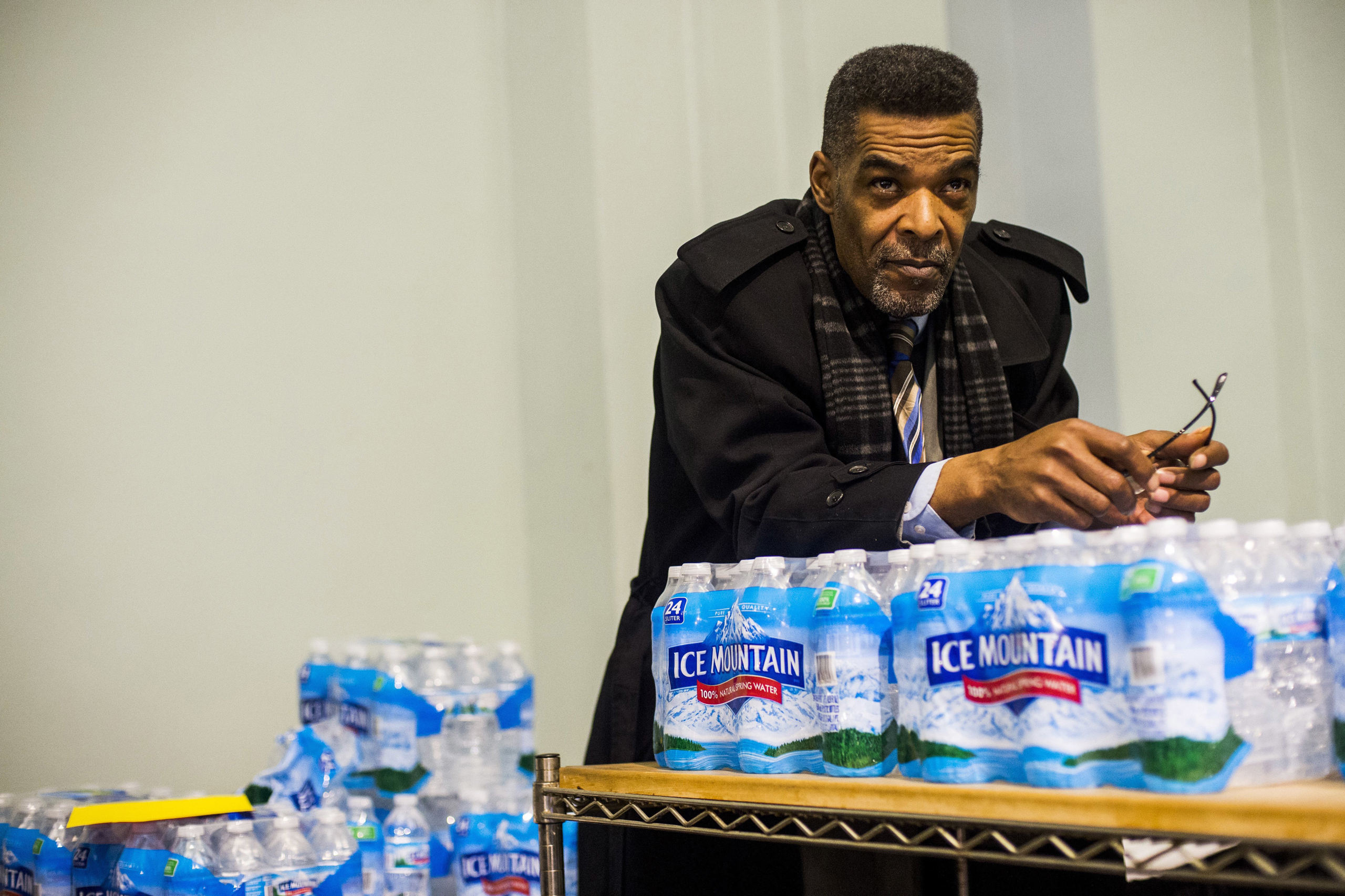 Flint City Councilman Eric Mays leans on a palette of water as he listens to health officials answer residents' questions during a Flint water town hall meeting at the University of Michigan-Flint Northbank Center in Flint, Mich., on Jan 12, 2017.