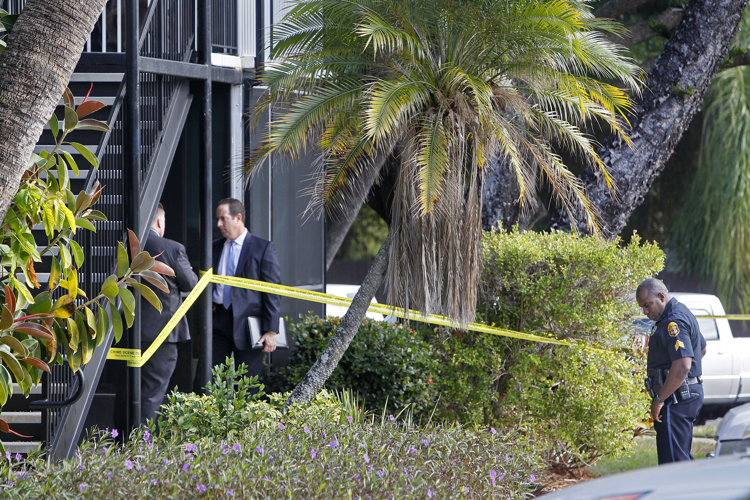 Clearwater Police detectives and an officer stand outside the ground floor apartment where a 10-year-old boy was fatally shot in his home in Clearwater, Fla., on Jan. 5, 2017.