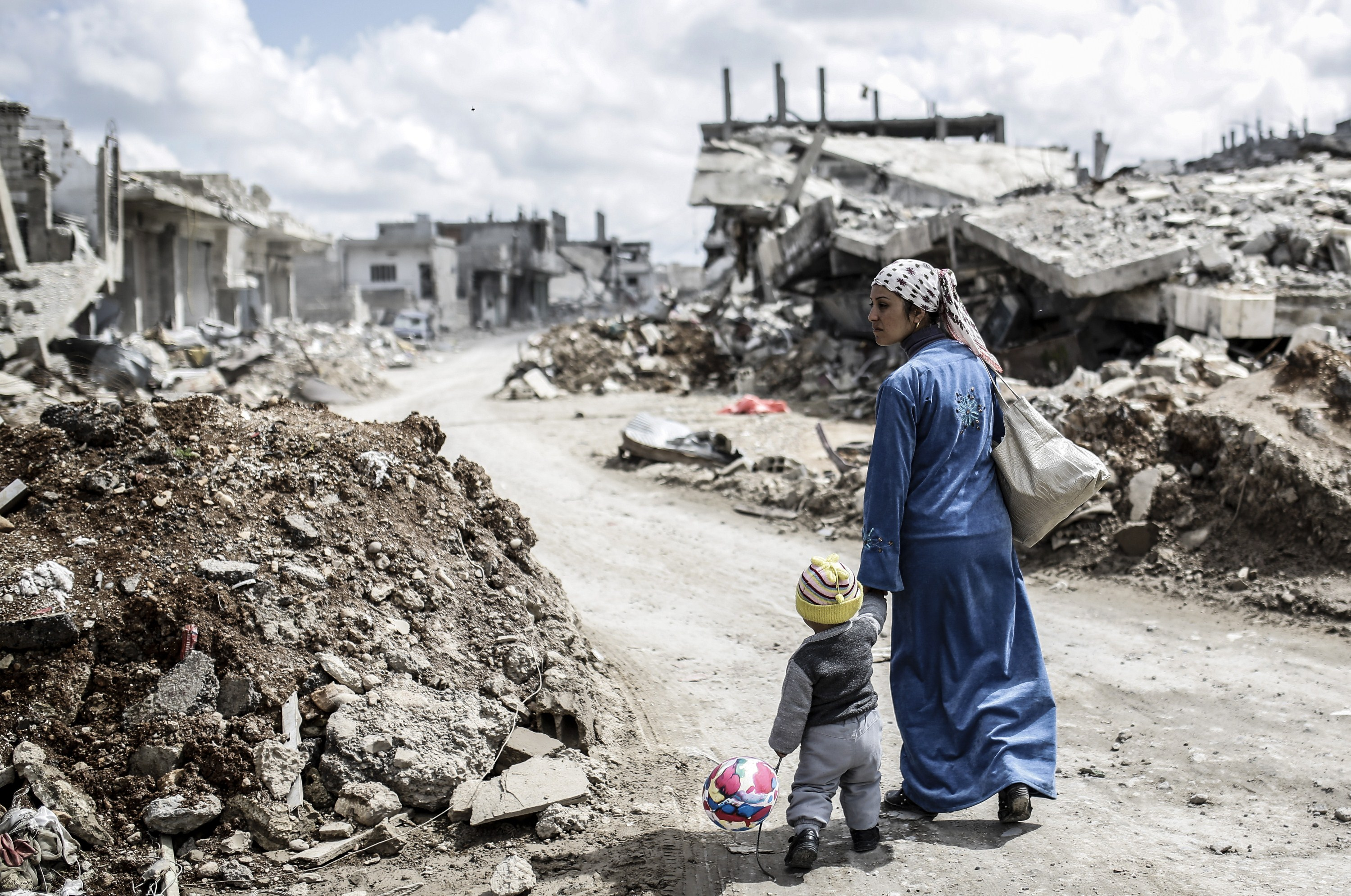 A Kurdish Syrian woman walks with her child past the ruins of the town of Kobane, also known as Ain al-Arab, on March 25, 2015.