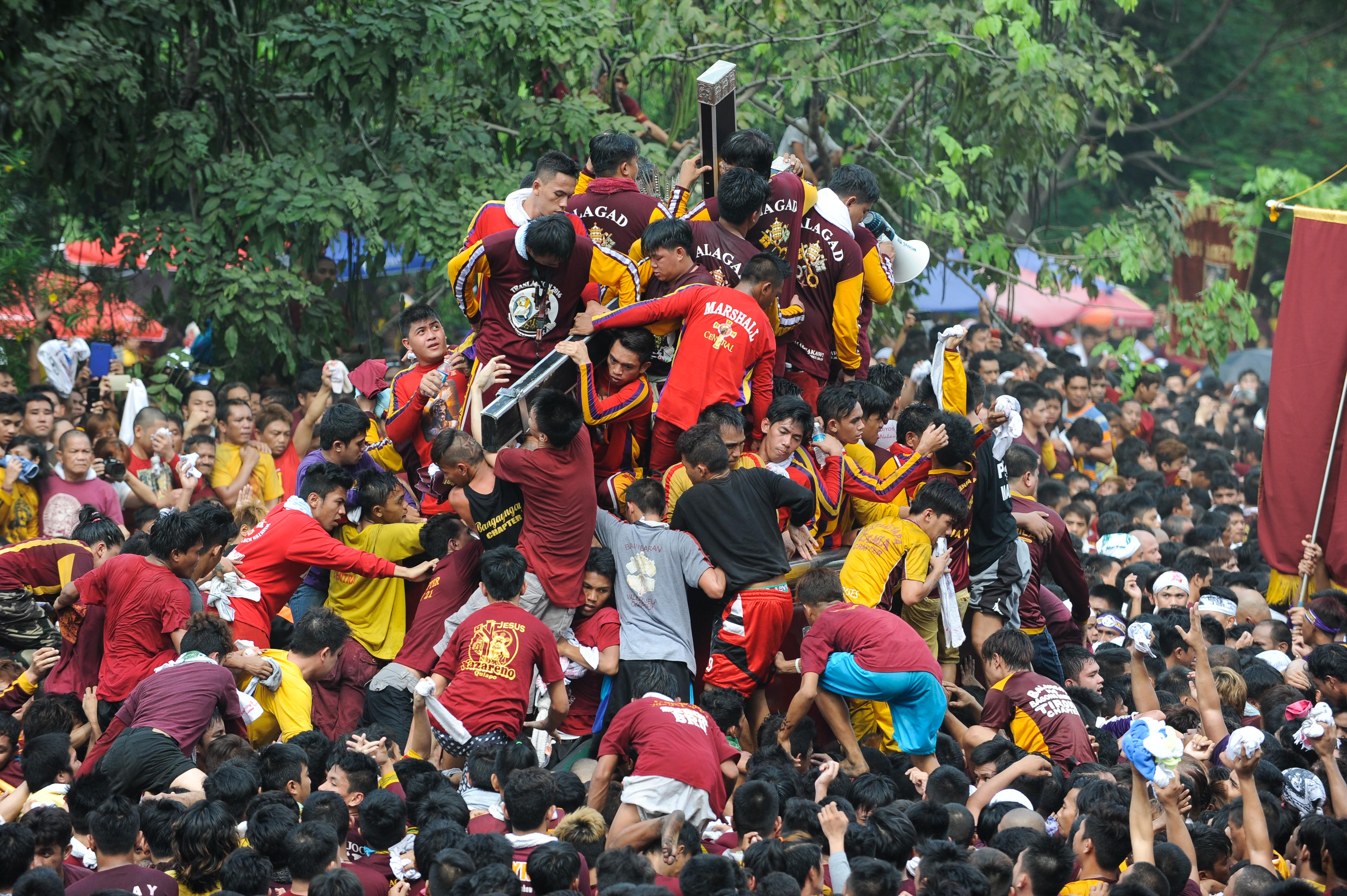 Devotees climb the carriage of the Black Nazarene during the Feast of the Black Nazarene on Jan. 9, 2016, in Manila