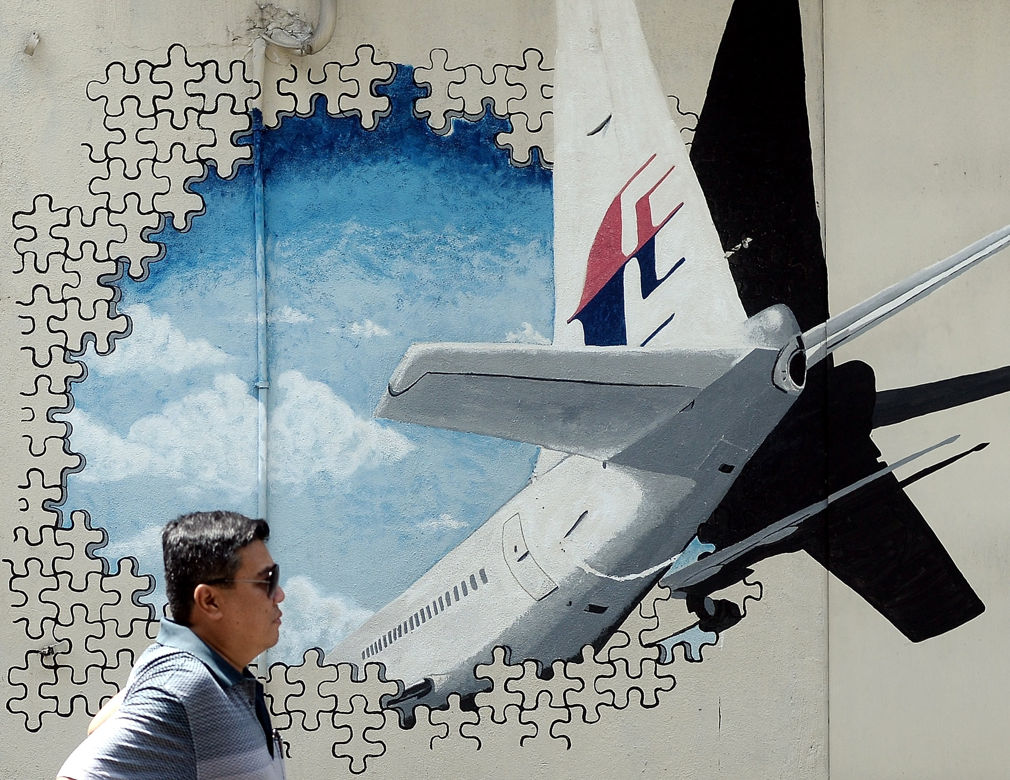 A Malaysian man walks in front of a mural of missing Malaysia Airlines MH370 plane in a back-alley in Shah Alam on March 8, 2016.