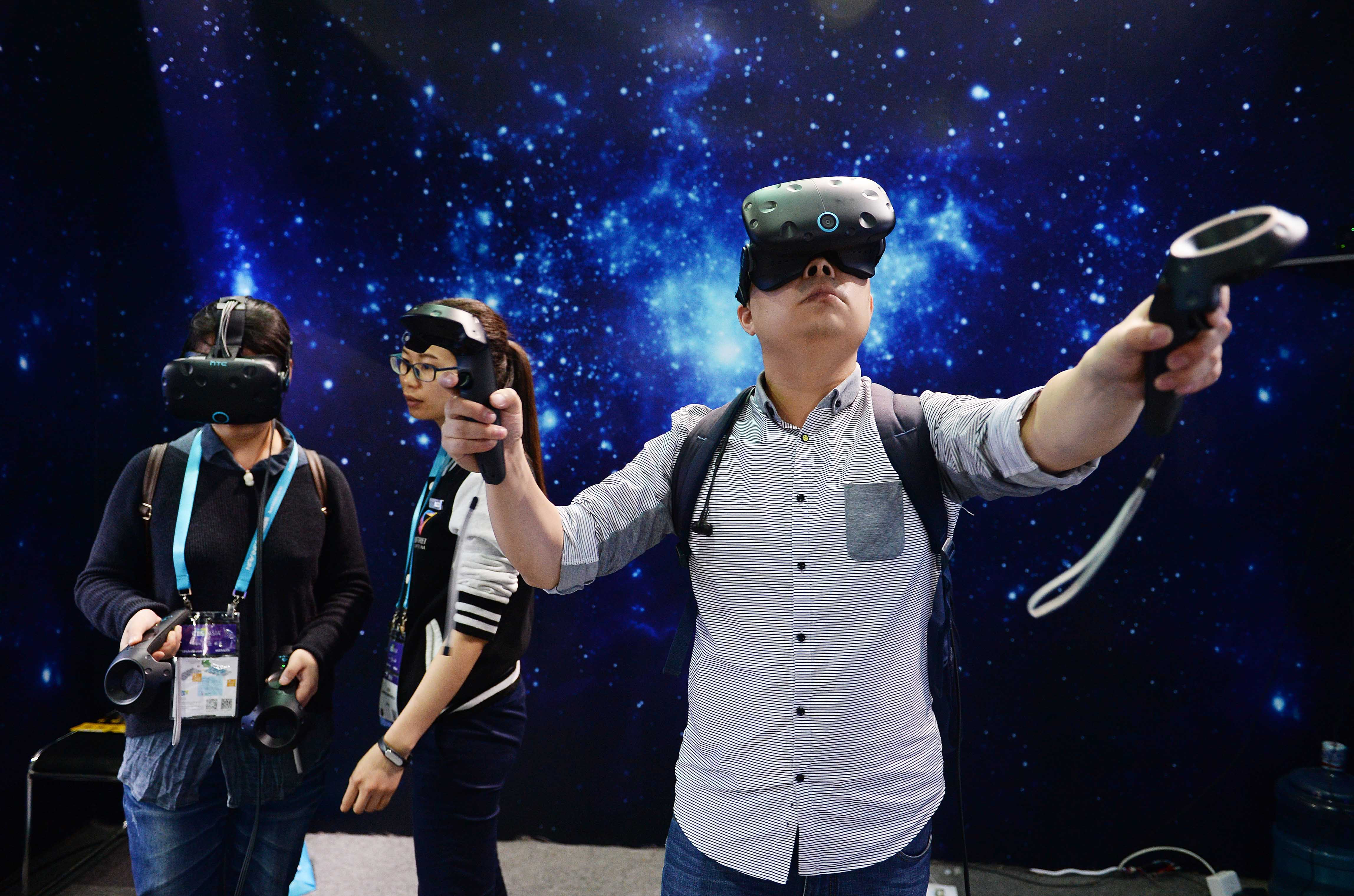 Visitors experience VR (virtual reality) devices during the CES Asia 2016 on May 11, 2016 in Shanghai, China.