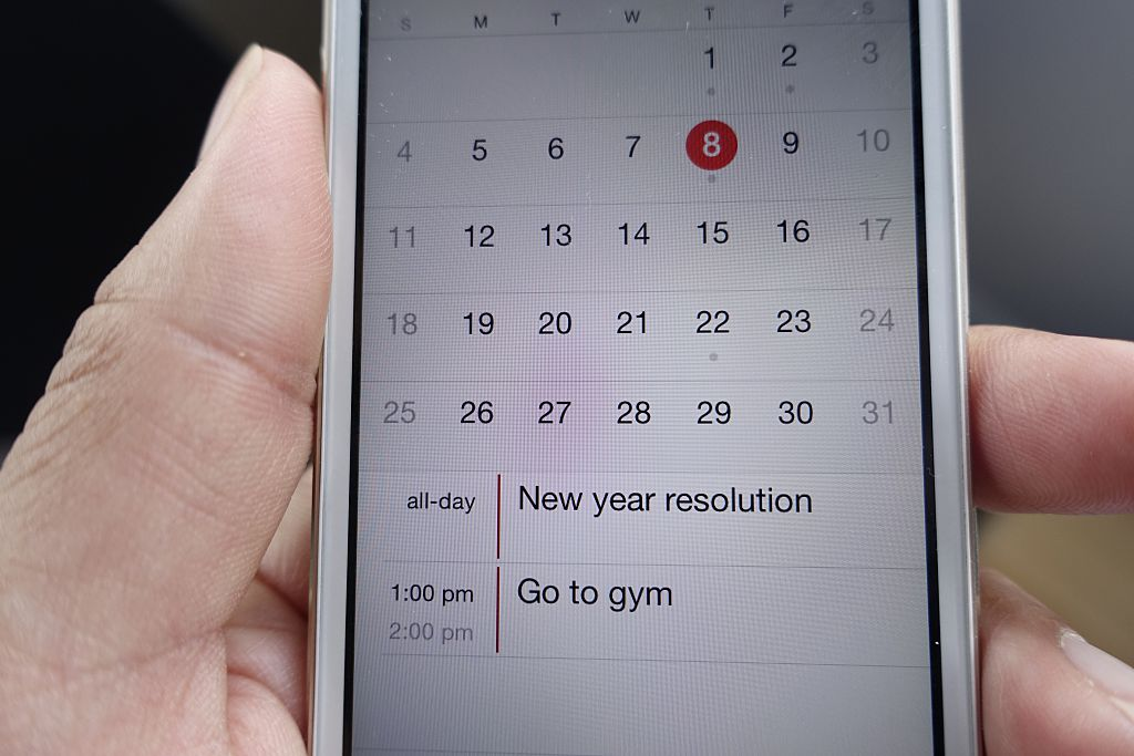 Female hand holding mobile phone with new year resolution reminder to go to gym.