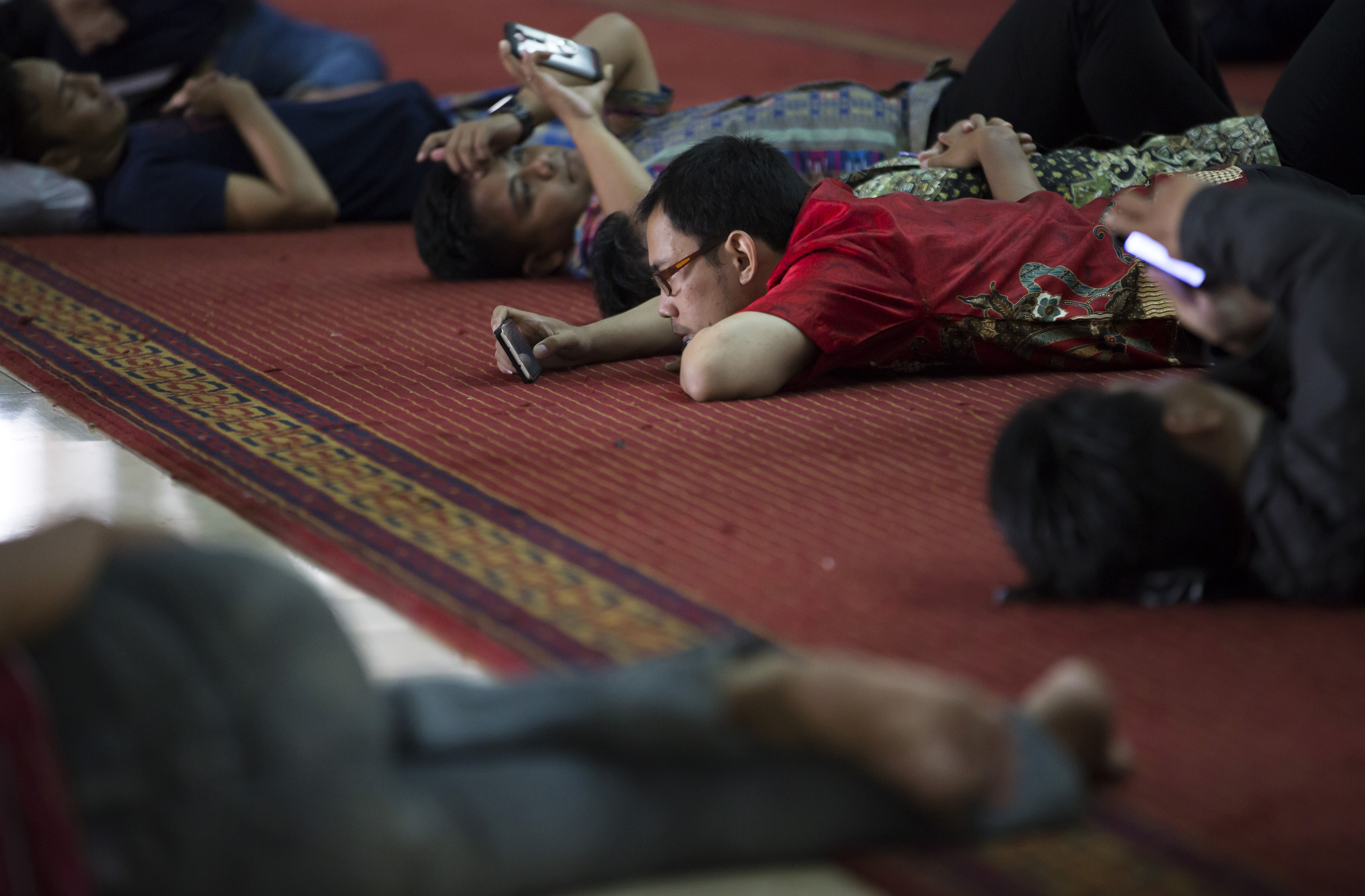 Muslims use smartphones as they rest after attending Friday prayers at the Istiqlal Mosque on Sept. 30, 2016, in Jakarta