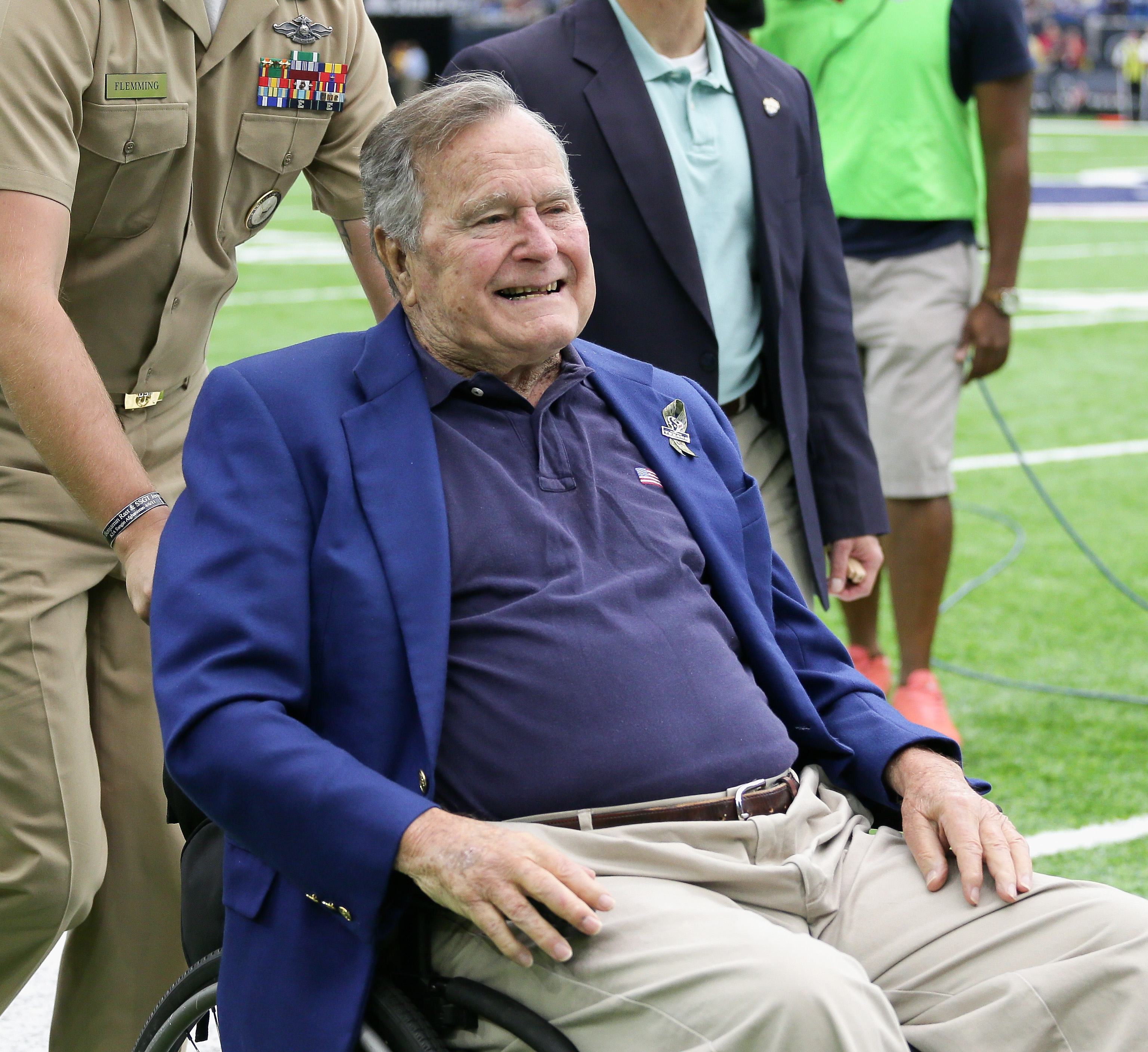 President George H.W. Bush is taken off the field after flipping the coin between the Detroit Lions and Houston Texans at NRG Stadium on October 30, 2016 in Houston, Texas.