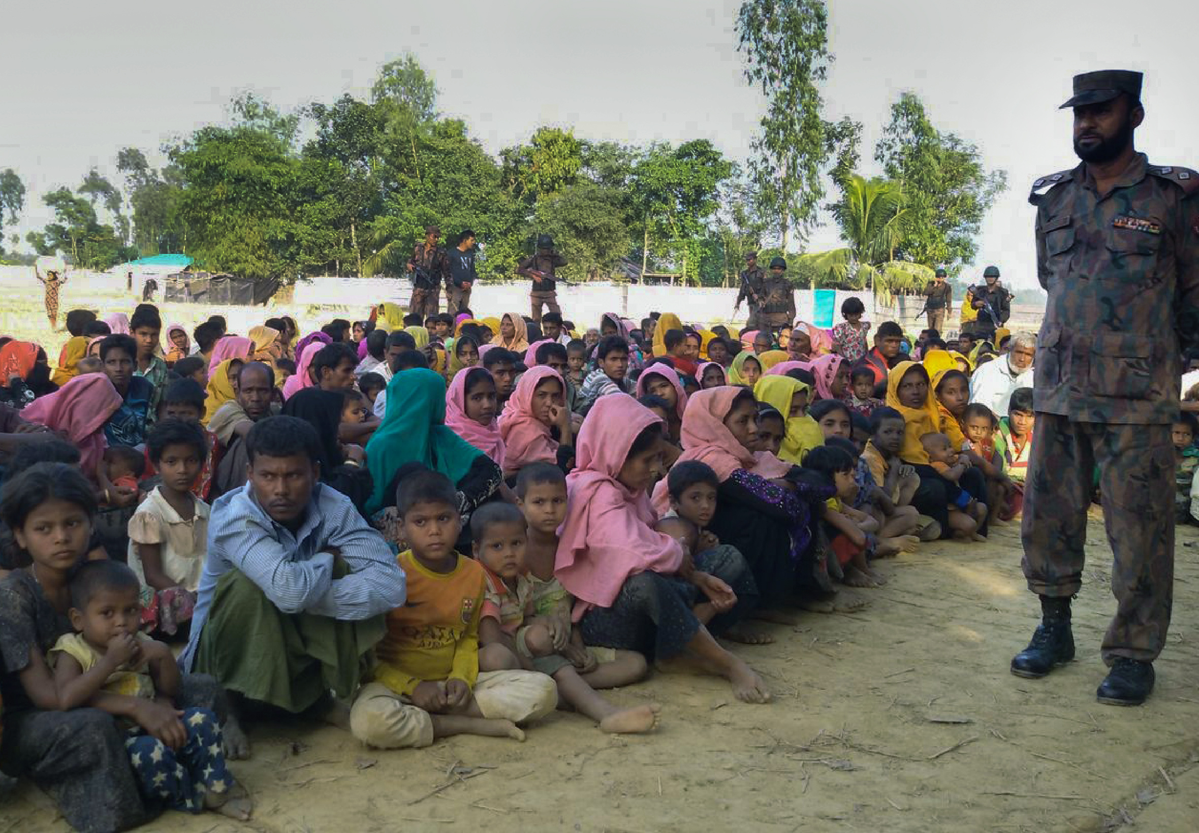 Rohingya Muslims from Burma, who tried to cross the Naf river into Bangladesh, are kept under watch by security officials in Teknaf, in Bangladesh, on Dec. 25, 2016.