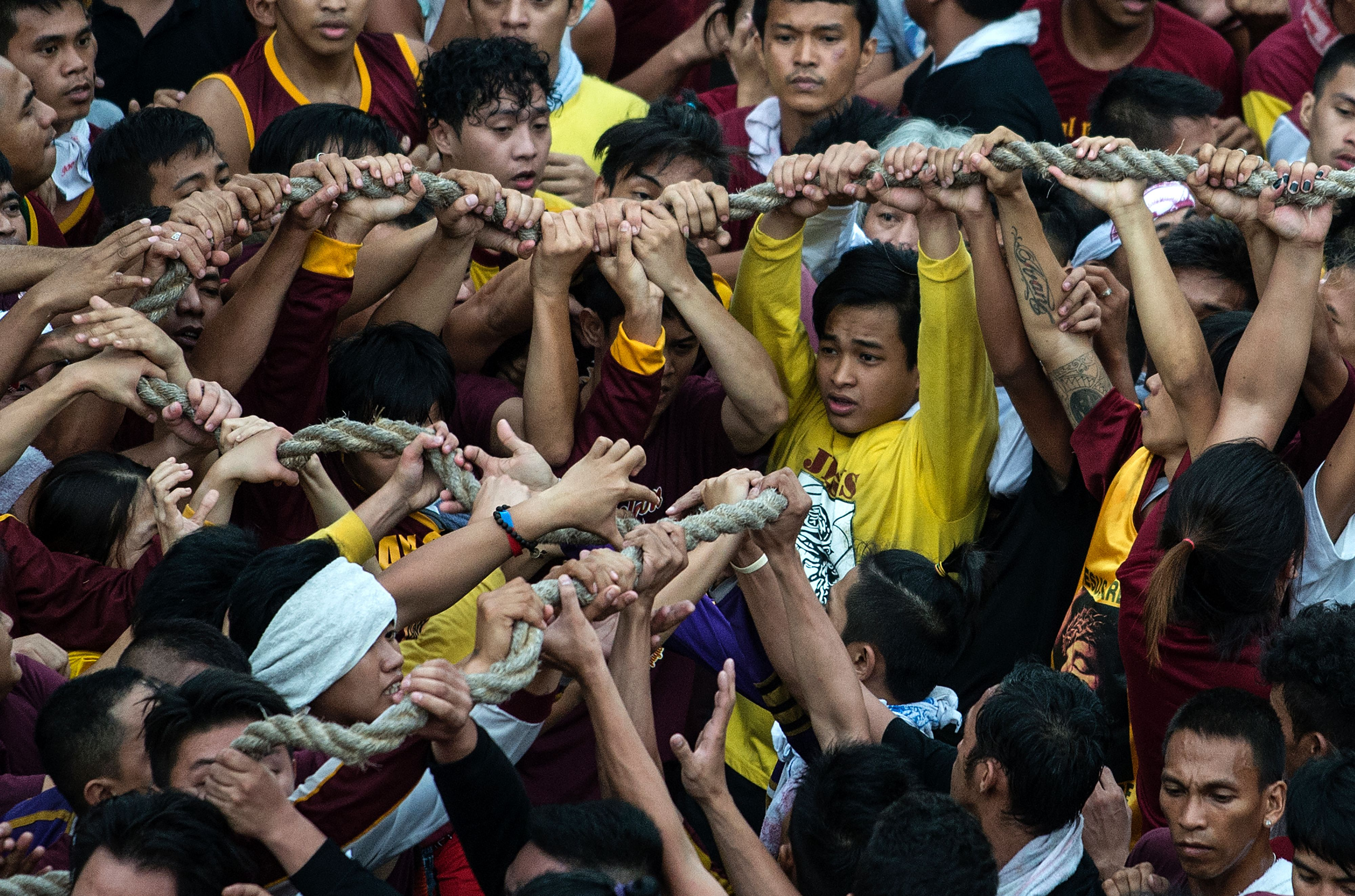 Devotees touch the rope used to pull the carriage carrying the life-size statue of the Black Nazarene on Jan. 9, 2017