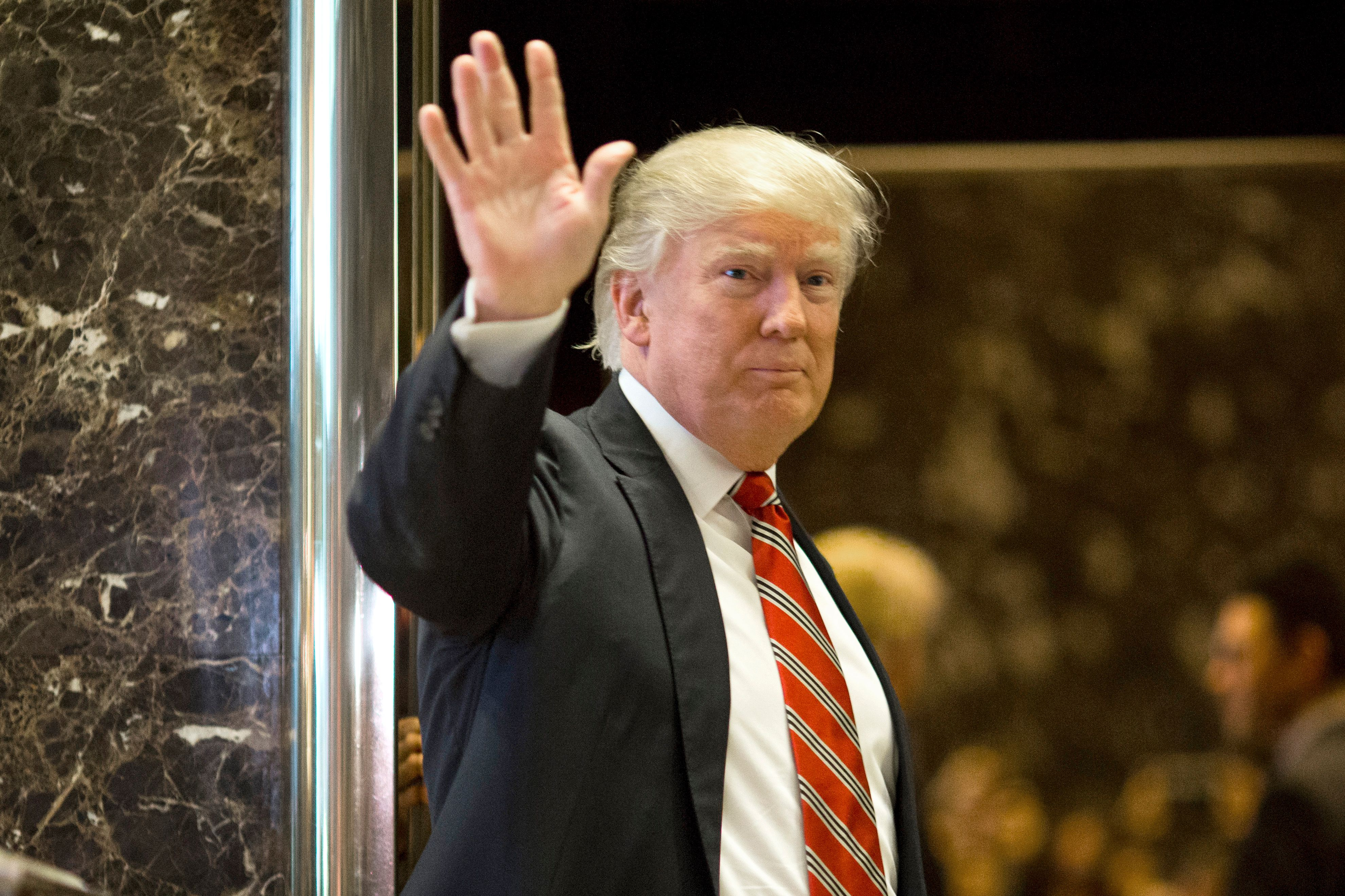 US President-elect Donald Trump waves toward the media after meeting Martin Luther King III at Trump Tower in New York City on January 16, 2017.