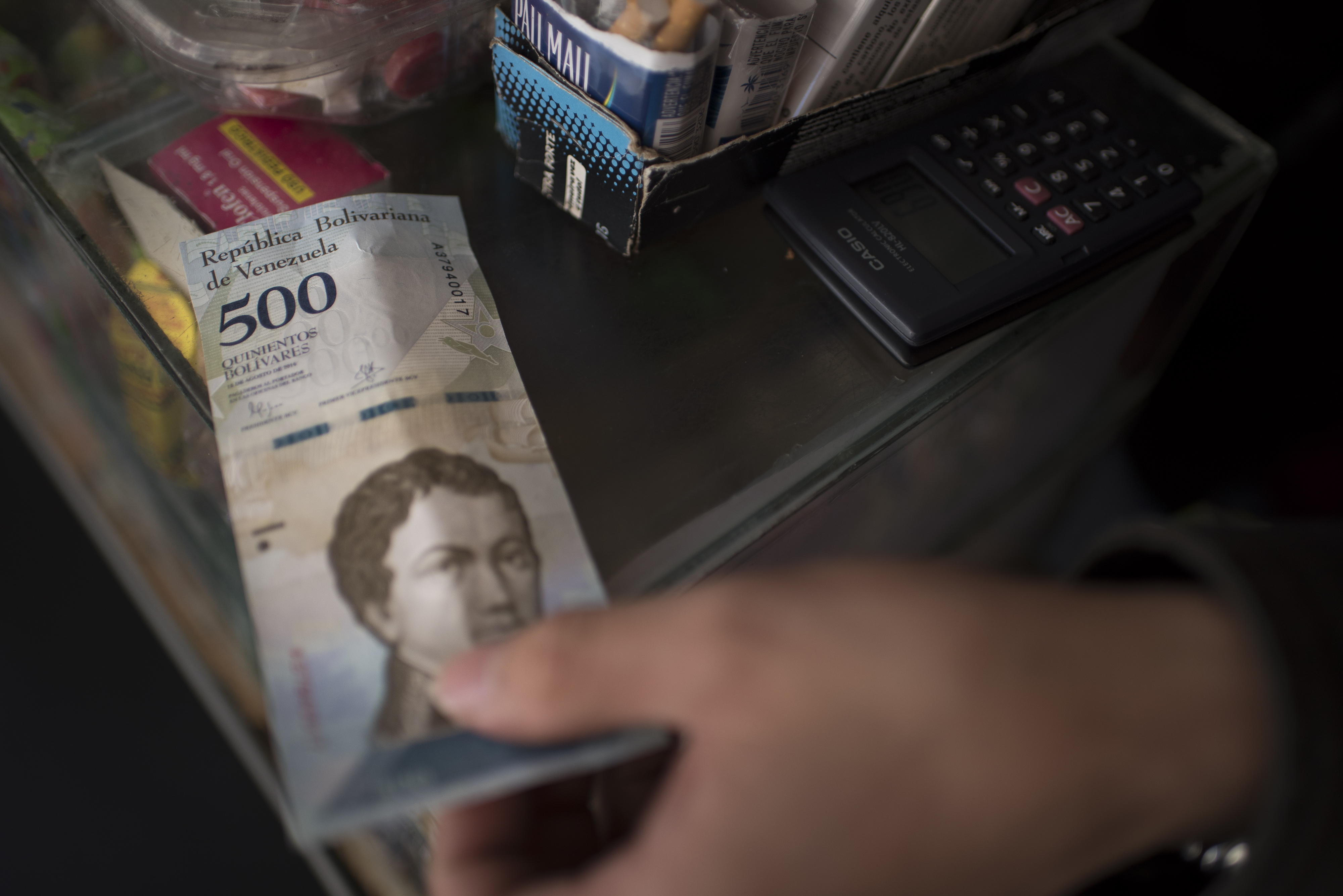 A vendor reaches a new 500-bolivar banknote from a customer at a stand in Caracas on Jan. 17, 2017