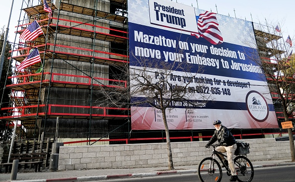 A man cycles past a giant banner, bearing a message of congratulations (Mazeltov) for incoming US President Donald Trump, covering a building under construction in central Jerusalem on Jan. 20, 2017.