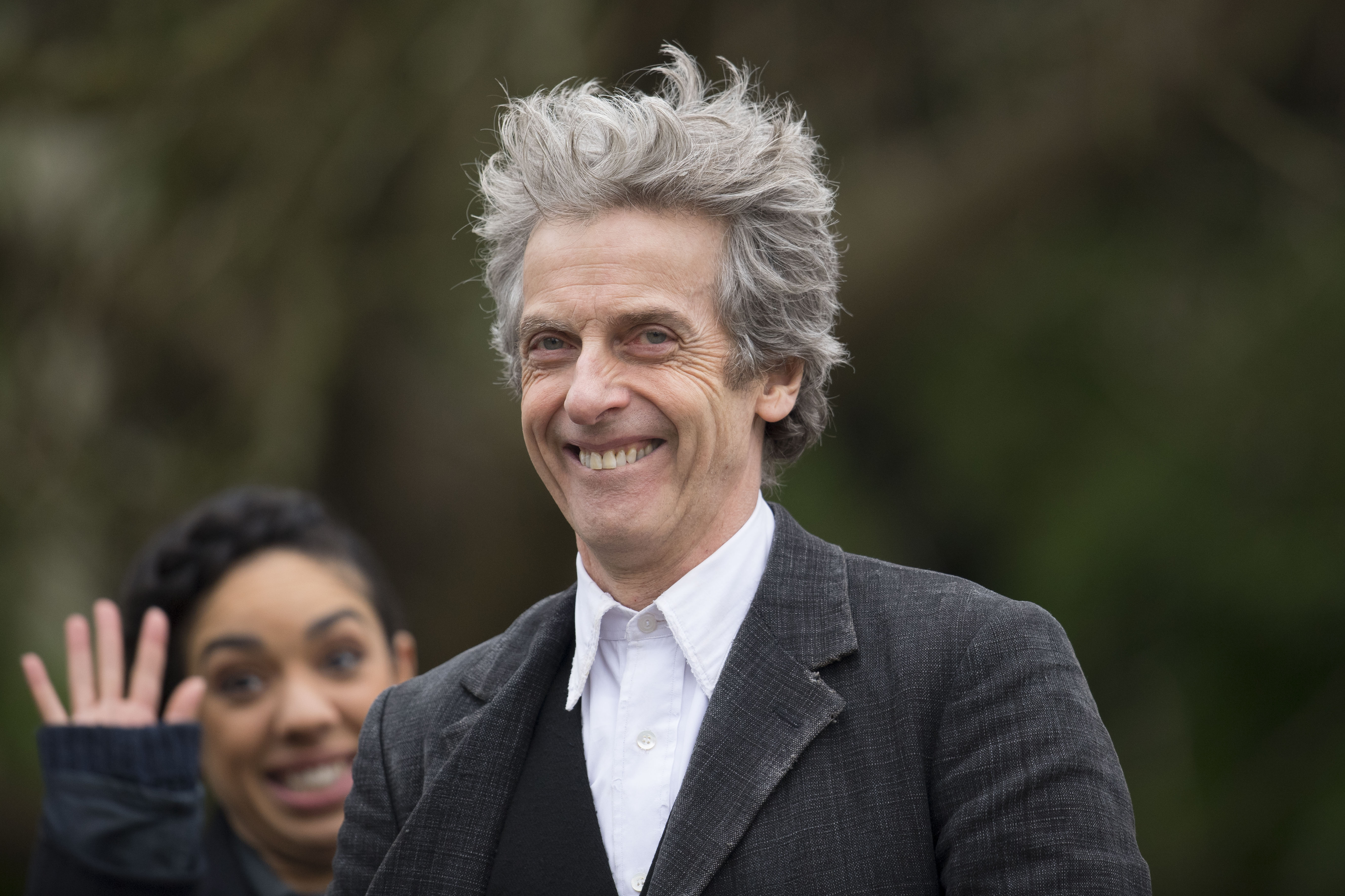 CARDIFF, WALES - JANUARY 26: Peter Capaldi, who plays the Doctor, smiles to the camera while the Doctor's companion Pearl Mackie waves during filming for series 10 of BBC show Doctor Who at Cardiff University's Main building on January 26, 2017  in Cardiff, Wales.
