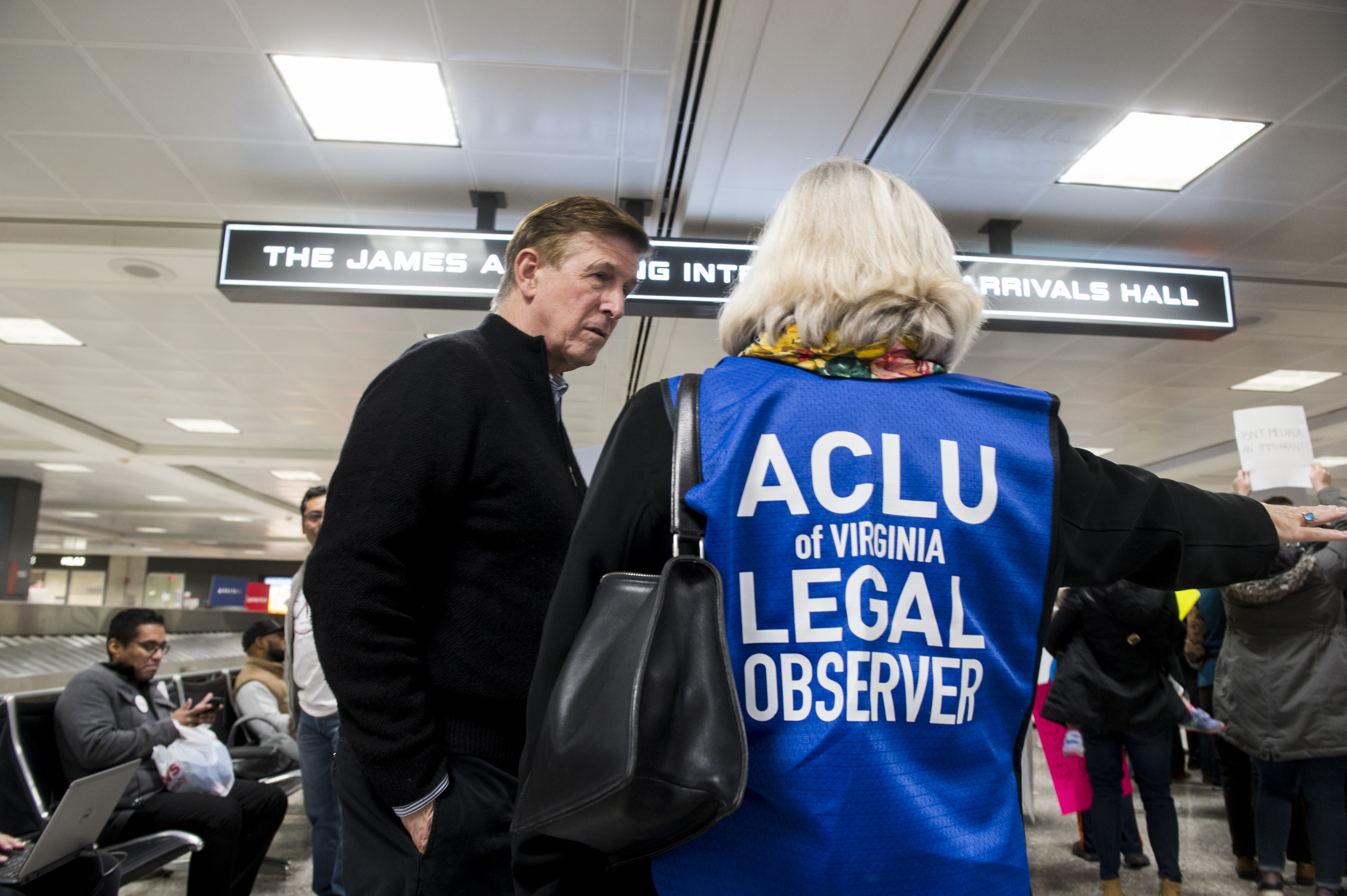 UNITED STATES - JANUARY 29: Rep. Don Beyer, D-Va., speaks with an ACLU legal observer during the protest at Dulles International Airport in Virginia on Sunday, Jan. 29, 2017. Protests erupted at airports around the country following President Trump's executive order restricting travel from several Islamic countries.