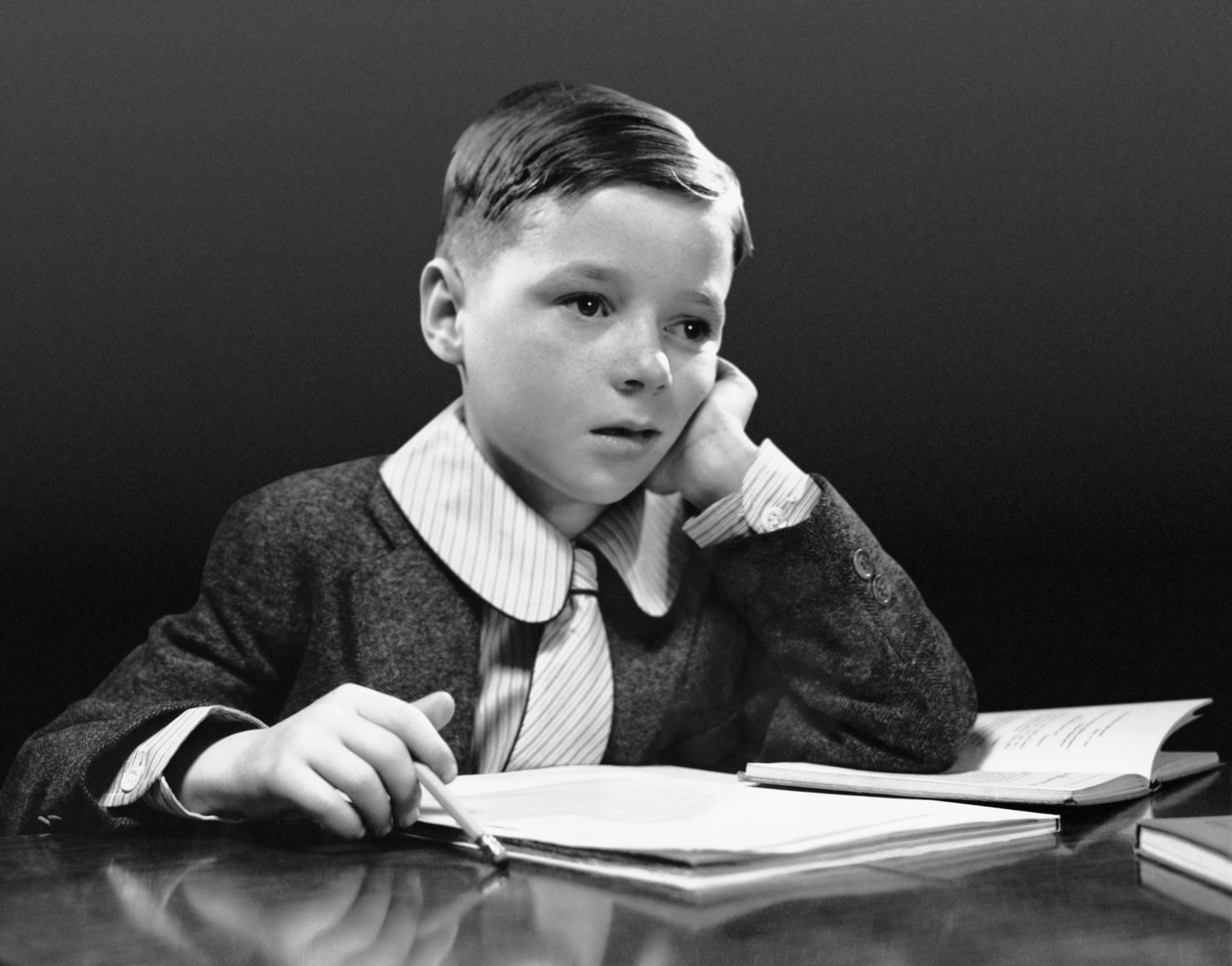 Boy sitting at desk with book.